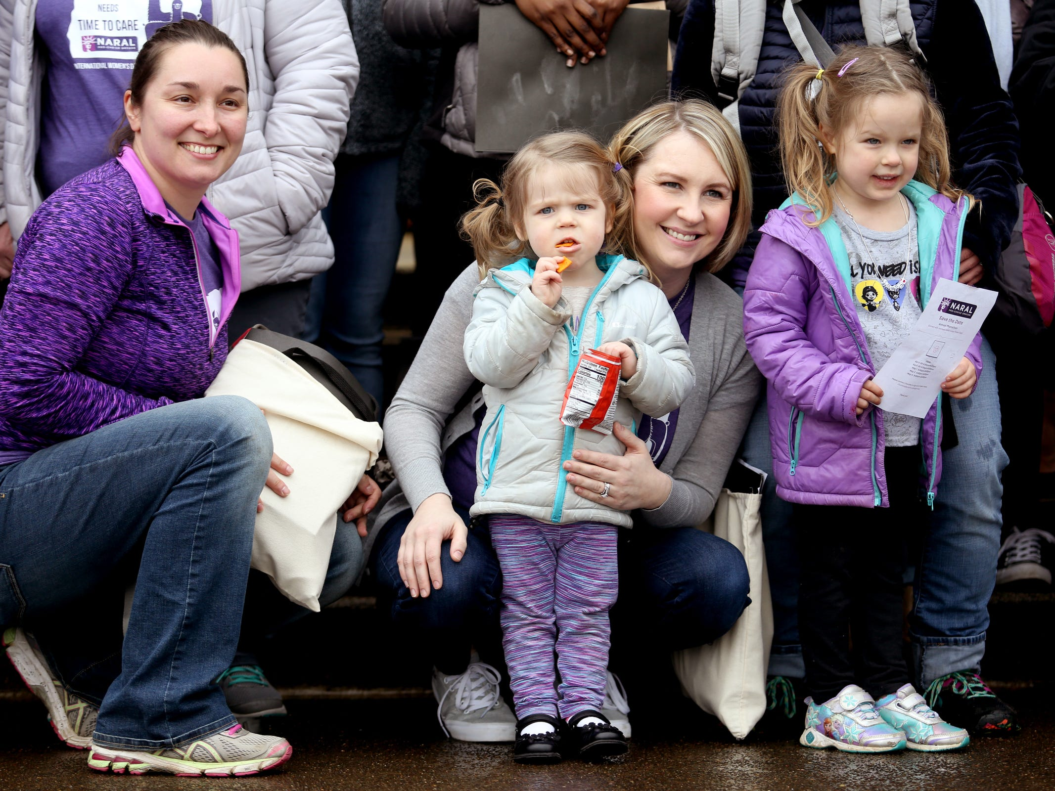 Ginni Garnes, 2, of Portland, snacks while having her photo taken with her mom, Marci Garnes, from left, family friend Joan Morgan, of Happy Valley, and sister Cordi Garnes, 4, during a demonstration for International Women's Day at the Oregon State Capitol in Salem on Friday, March 8, 2019. Many during the rally voiced their support for a state-run family and medical leave insurance program in Oregon.