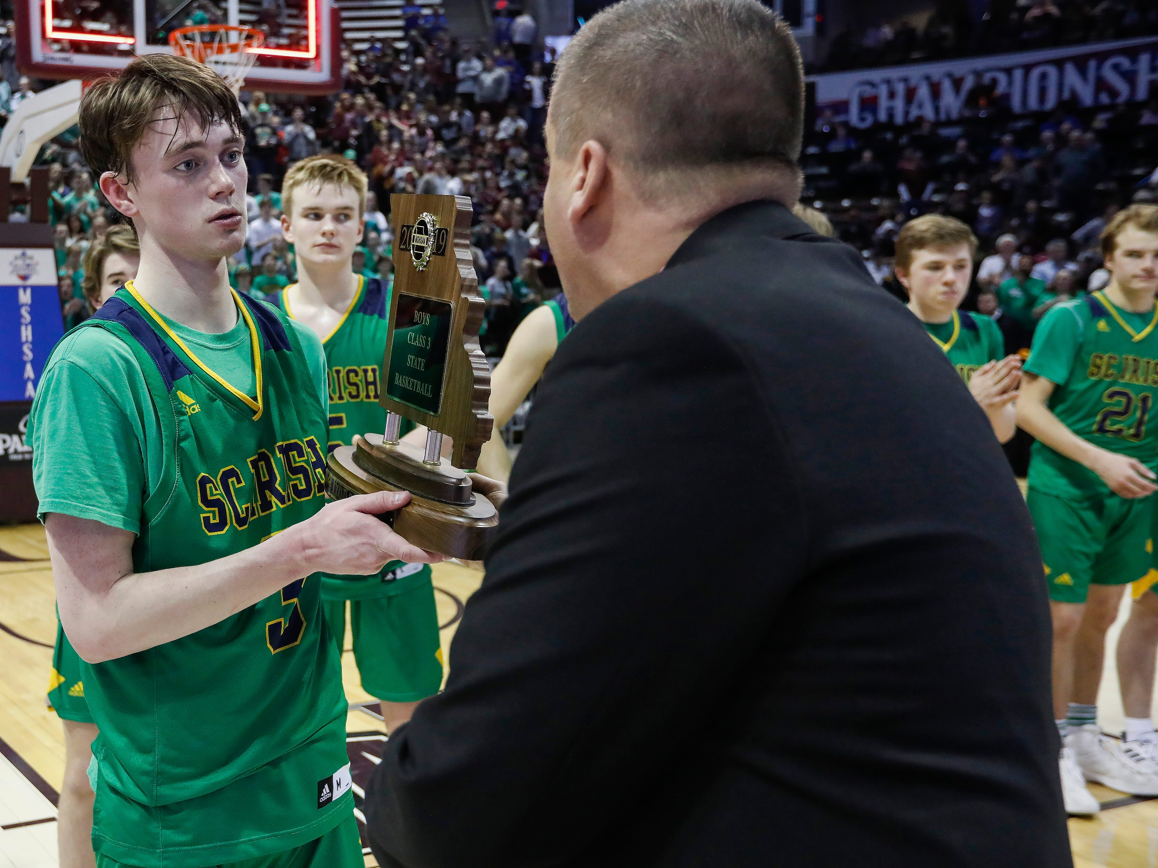 Jake Branham, of Springfield Catholic, accepts the 2nd place trophy after the Irish's 69-59 loss to Vashon in the Class 3 state championship game at JQH Arena on Friday, March 8, 2019.