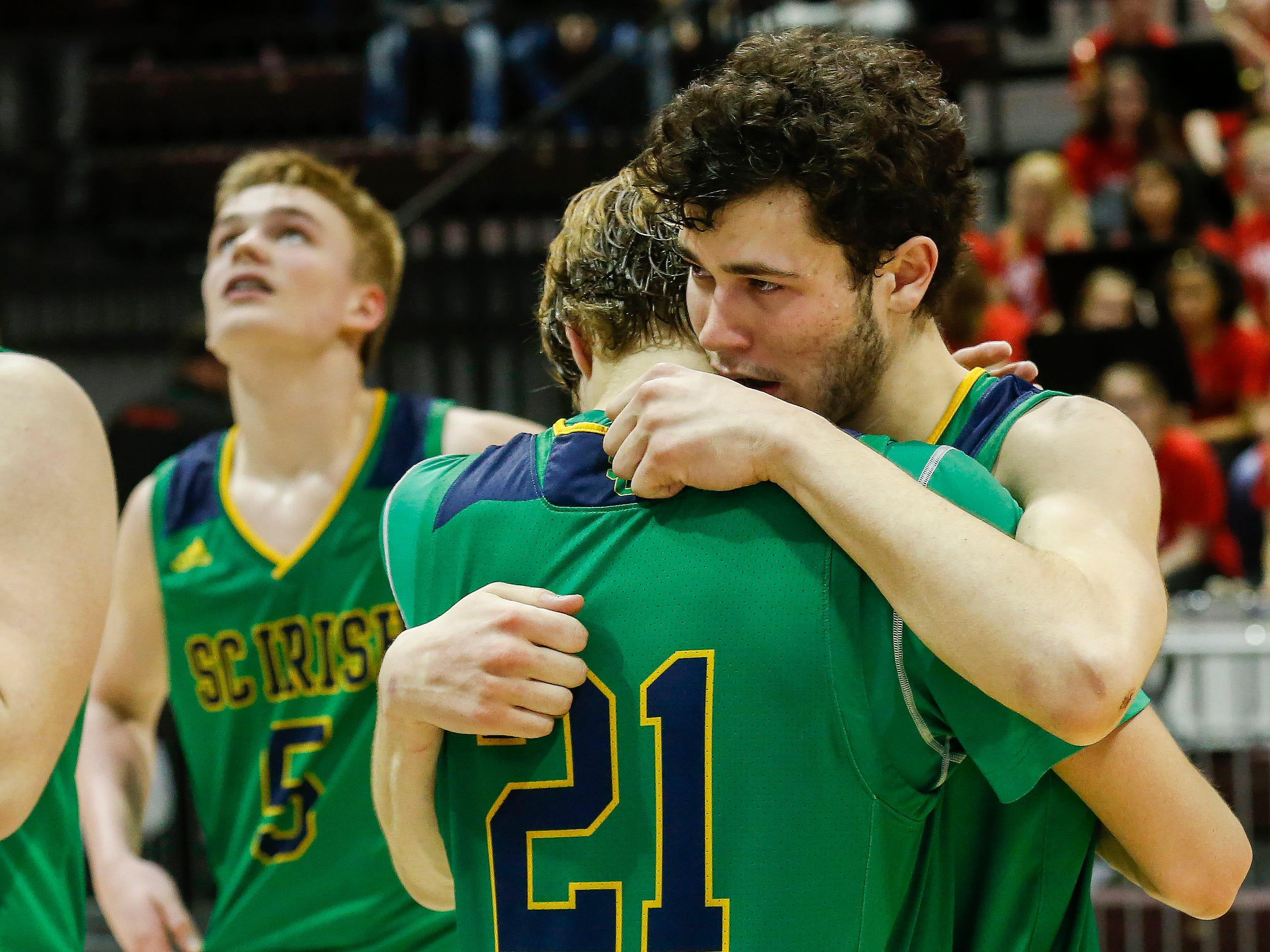 Charlie O'Reilly (21) and Michael Manzardo, of Springfield Catholic, console each other after the Irish's 69-59 loss to Vashon in the Class 3 state championship game at JQH Arena on Friday, March 8, 2019.