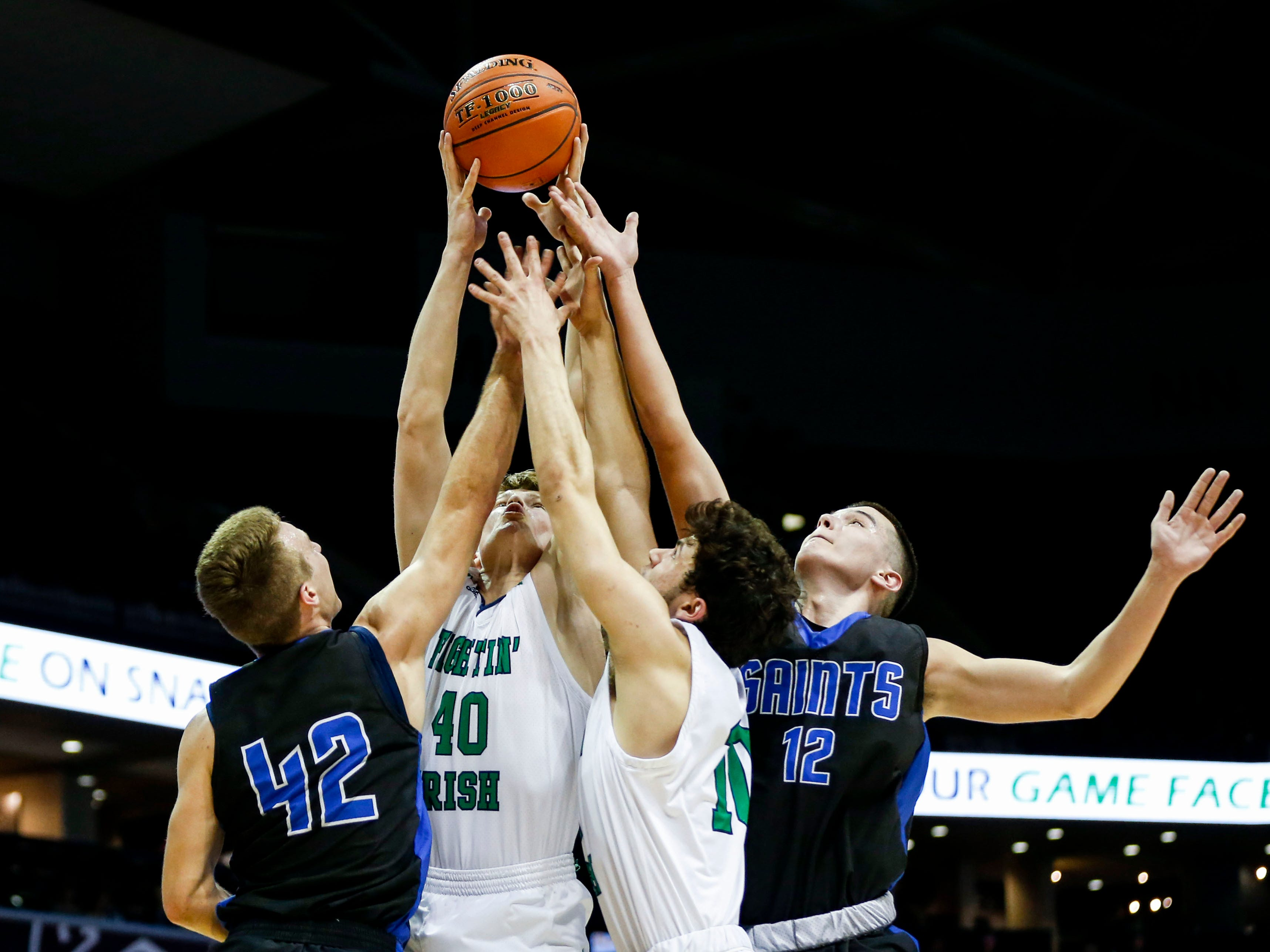 Springfield Catholic's Will Morrison gets his hands on a rebound as the Fightin' Irish take on the St. Paul Lutheran Saints in semifinal round of Class 3 state basketball at JQH Arena on Thursday, March 7, 2019.