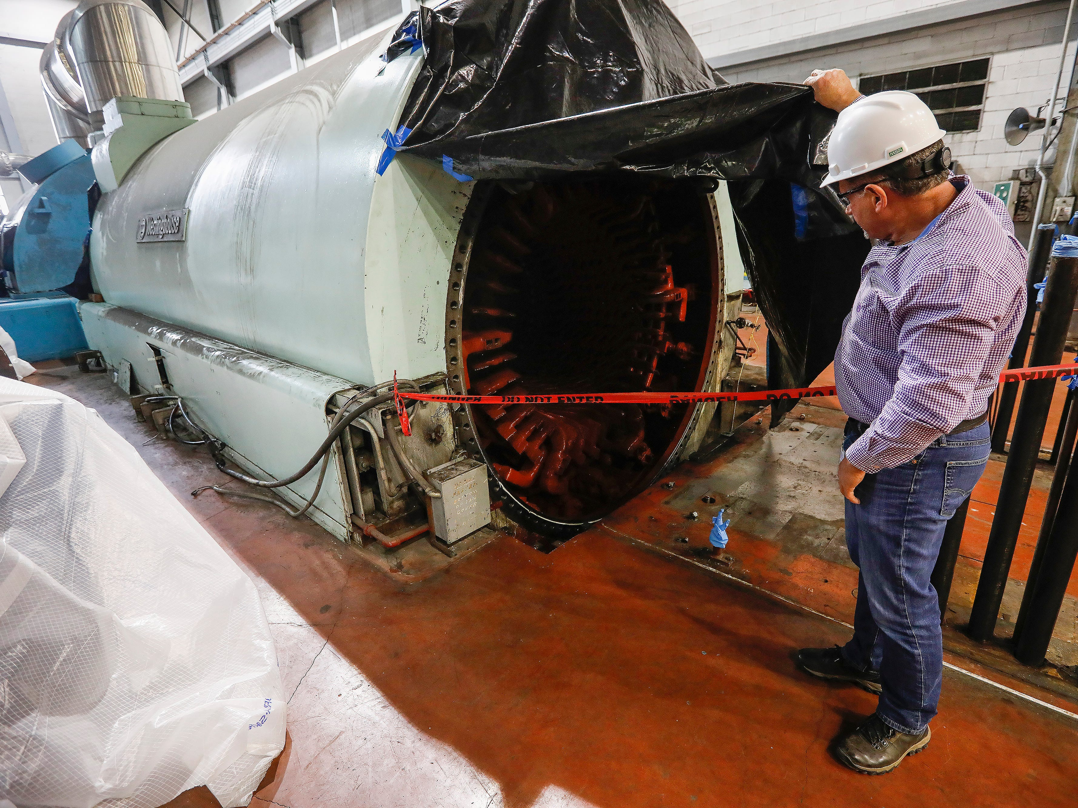 Willy Haffecke, director of power generation at the John Twitty Energy Center, shows where the turbine sits inside the generator.