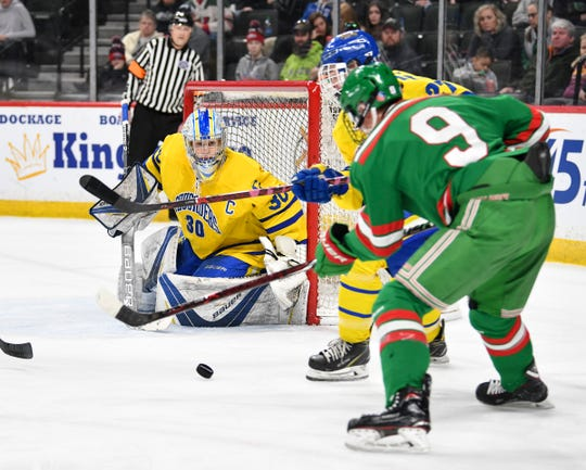 The puck skips past Cathedral goaltender Noah Amundson during the first period of the 2019 state tournament championship semifinals game against East Grand Forks Friday, March 8, at the Xcel Energy Center in St. Paul.