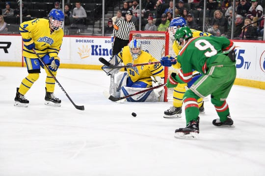 St. Cloud Cathedral and East Grand Forks players battle for the puck Friday in their Class A semifinal game.