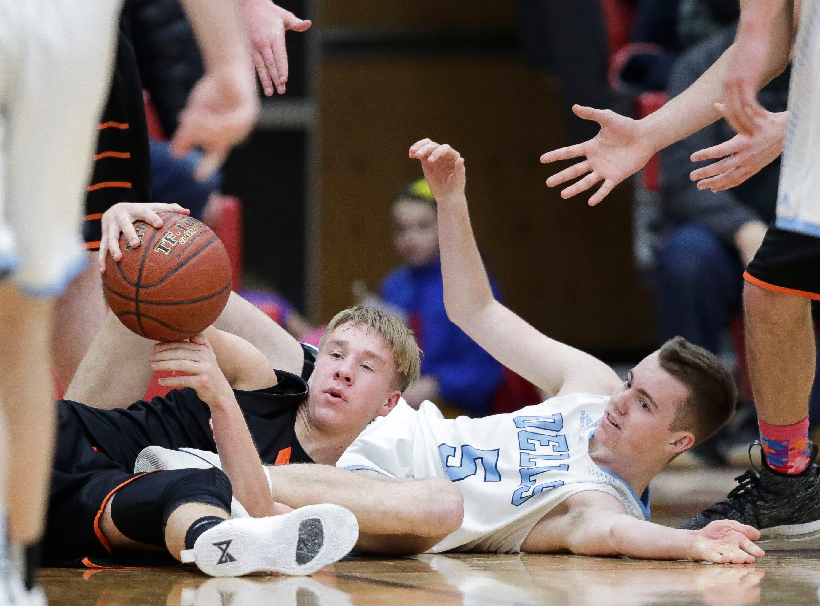 Stratford's Chandler Schmidt (11) and Wisconsin Dells' Sam Millard (5) fight for a loose ball in a Division 3 sectional semifinal on Thursday, March 7, 2019, at Stevens Point Area High School in Stevens Point, Wis. Tork Mason/USA TODAY NETWORK-Wisconsin