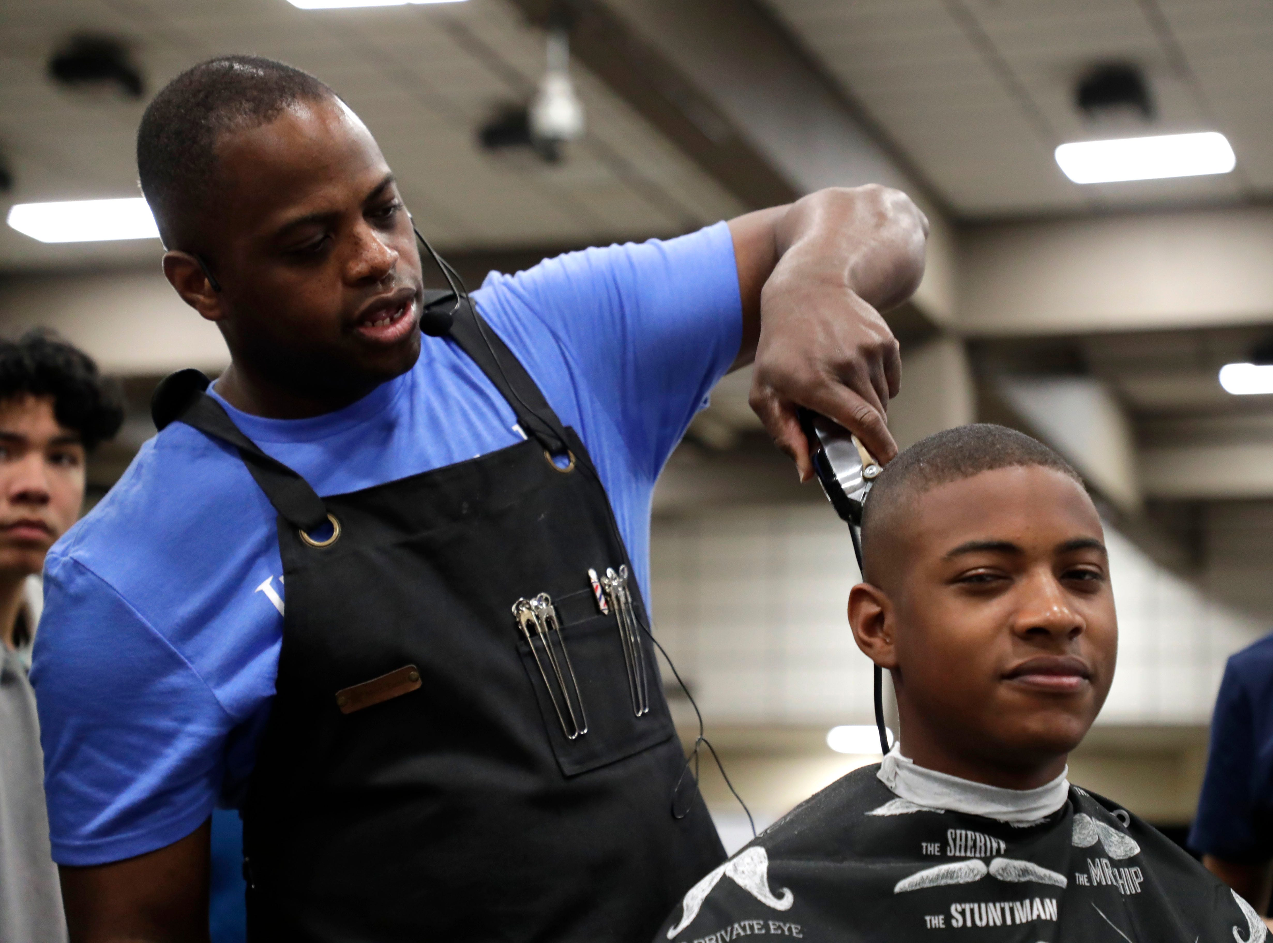 An instructor for the Lively Technical Center barber program, Mahir Rutherford, left, demonstrates a fade technique on his son Mahir Rutherford Jr. High school students throughout Leon County attended the Leon Works Expo at the Tucker Civic Center Friday March 8, 2019.