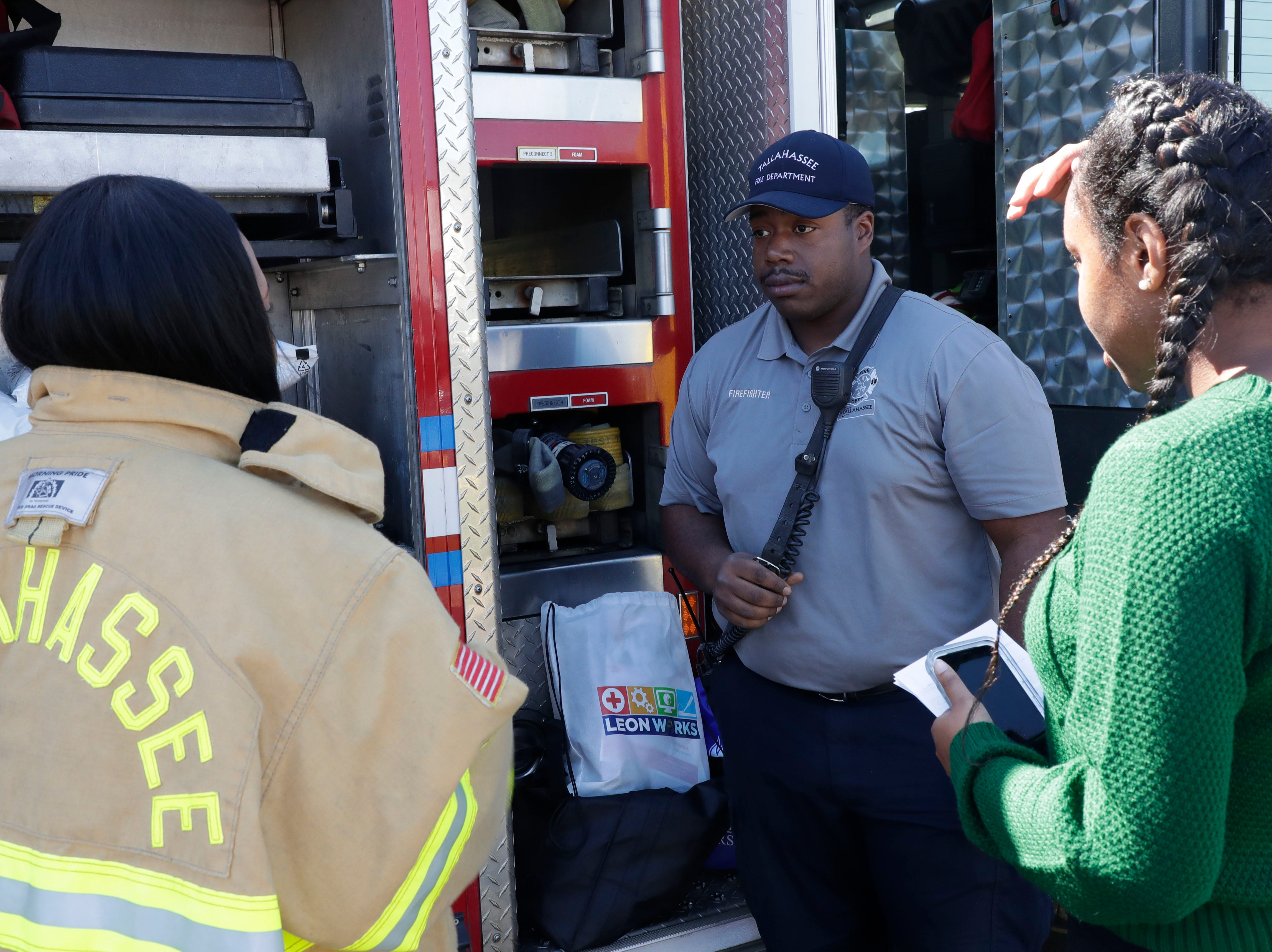 Delano Johnson, a firefighter with the Tallahassee Fire Department, center, talks to Rickards High School seniors, Joy Kelly, left, and Ashley Norton about a future in fighting fires. High school students throughout Leon County attended the Leon Works Expo at the Tucker Civic Center Friday March 8, 2019.