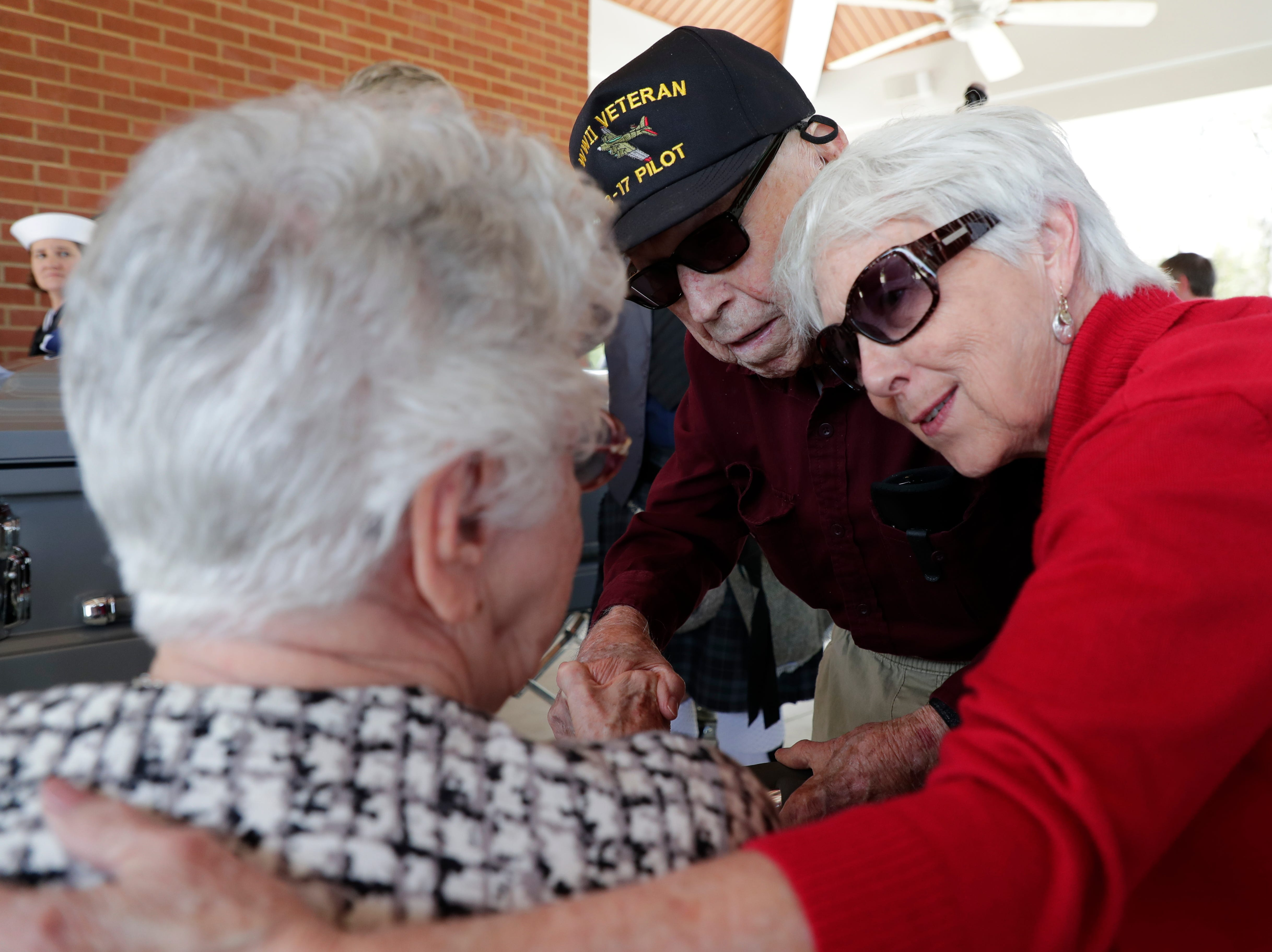 Emily Golz, sister of Earl Paul Baum, a sailor who was killed in Pearl Harbor, left, receives condolences from family friends Bill Bigham, center, and his daughter Patty Williams. A funeral was held at the Tallahassee National Cemetery honoring Baum Friday, March 8, 2019.