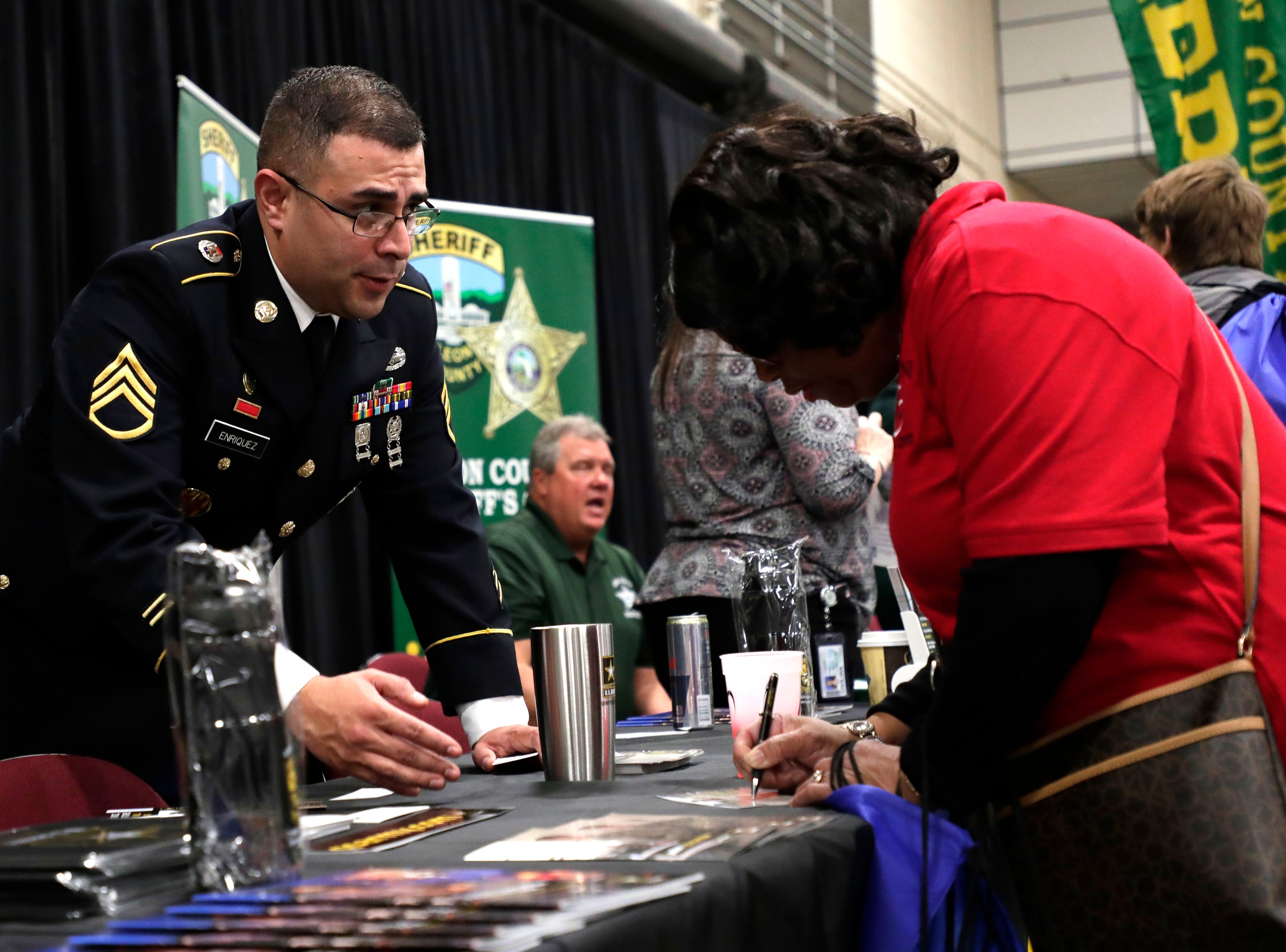 Staff Sergeant Eneiquwz, an army recruiter, left, talks to Patricia Zackery about a future in the army. High school students throughout Leon County attended the Leon Works Expo at the Tucker Civic Center Friday March 8, 2019.