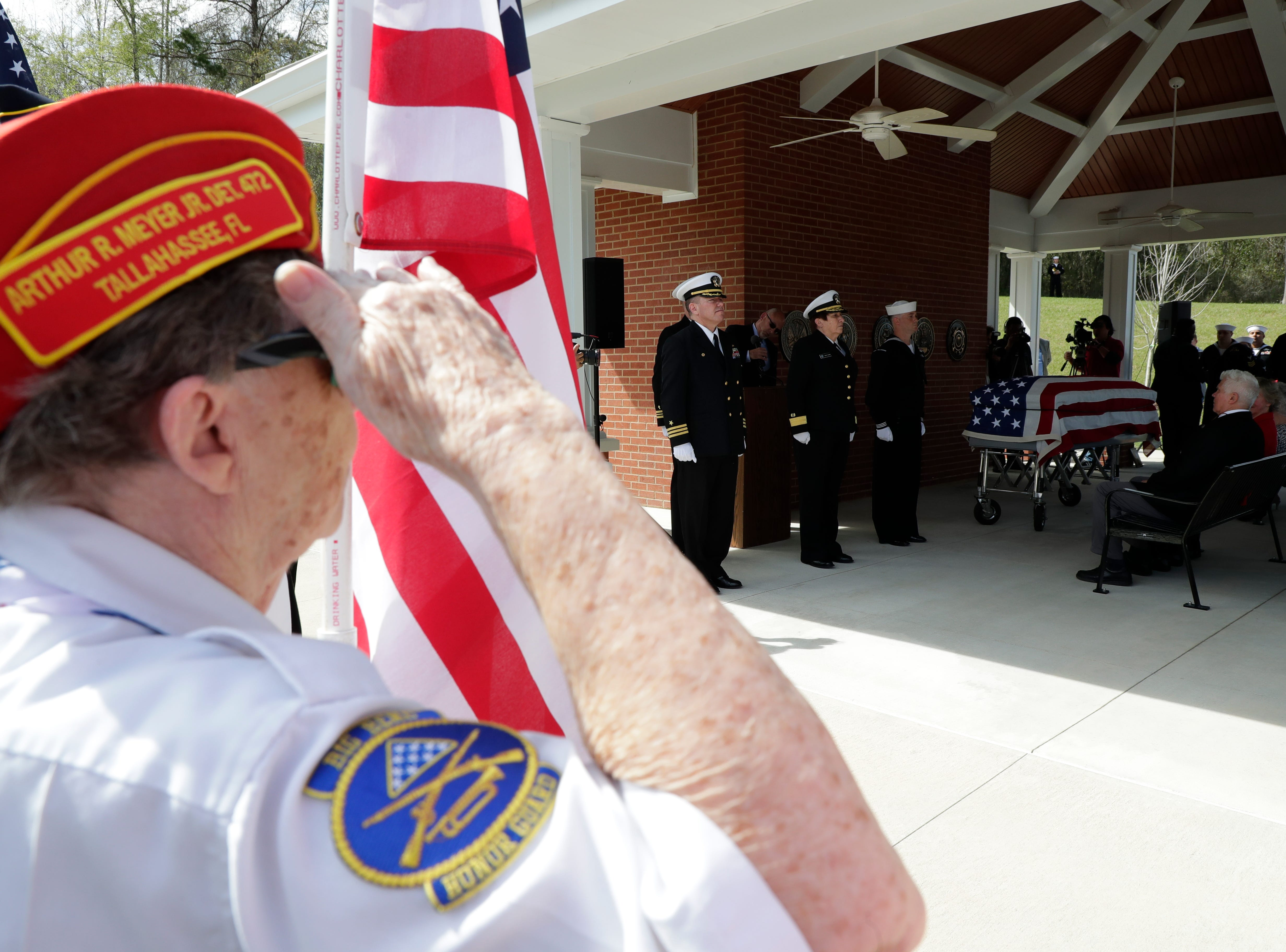 A member of the Big Bend Honor Guard holds an American flag as she salutes while the casket of Earl Baum, a sailor who was killed in Pearl Harbor, is placed for a funeral which was held at the Tallahassee National Cemetery Friday, March 8, 2019.