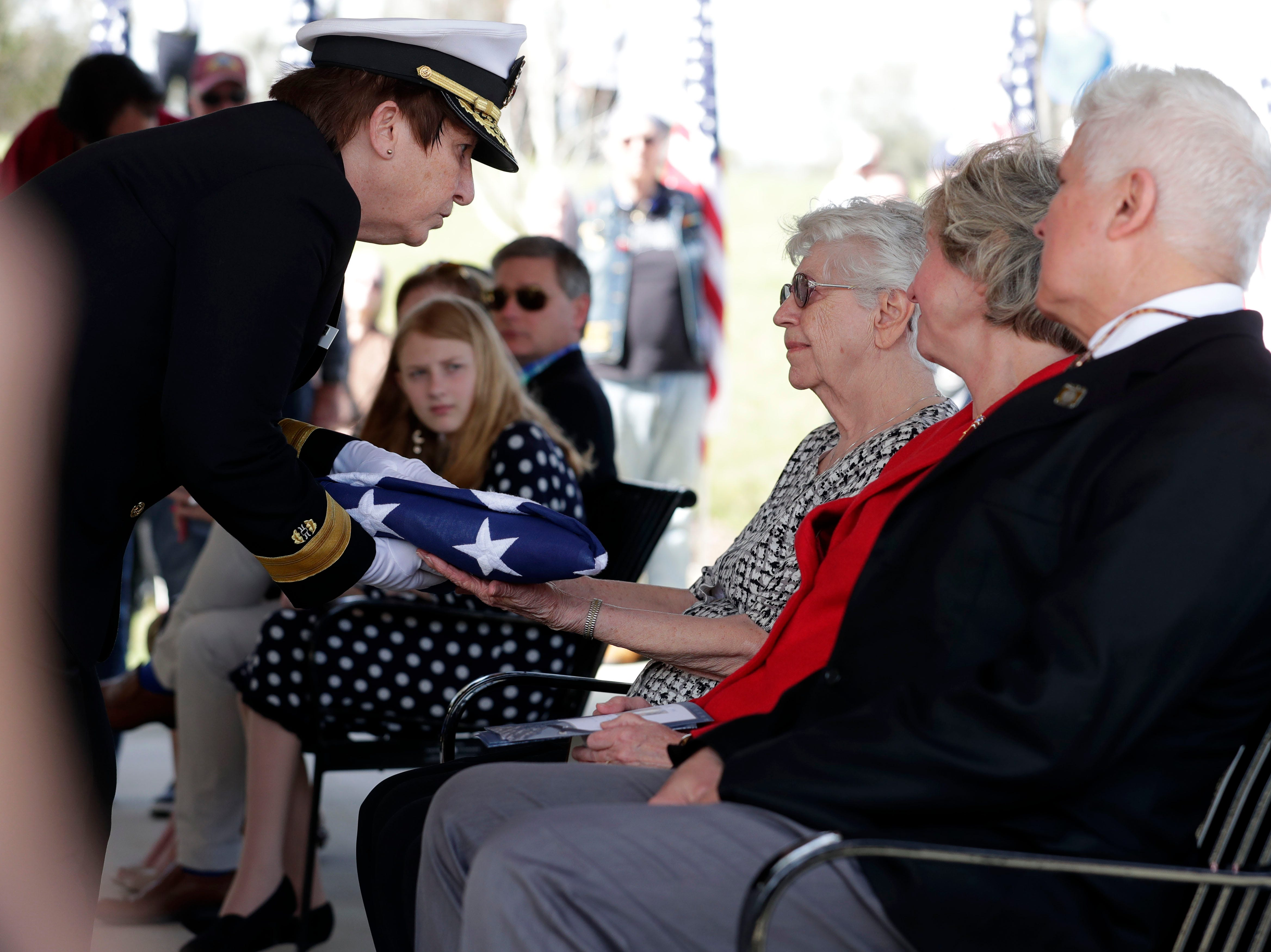 Emily Golz, sister of Earl Paul Baum, a sailor who was killed in Pearl Harbor, right, is handed the folded flag from her brother's casket. A funeral was held at the Tallahassee National Cemetery honoring Baum Friday, March 8, 2019.