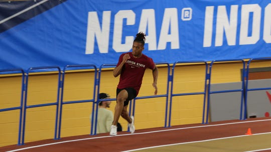 Florida State sprinter Kasaun James hits the turn during a practice run of the 200 at the NCAA Indoor Track & Field Championships.
