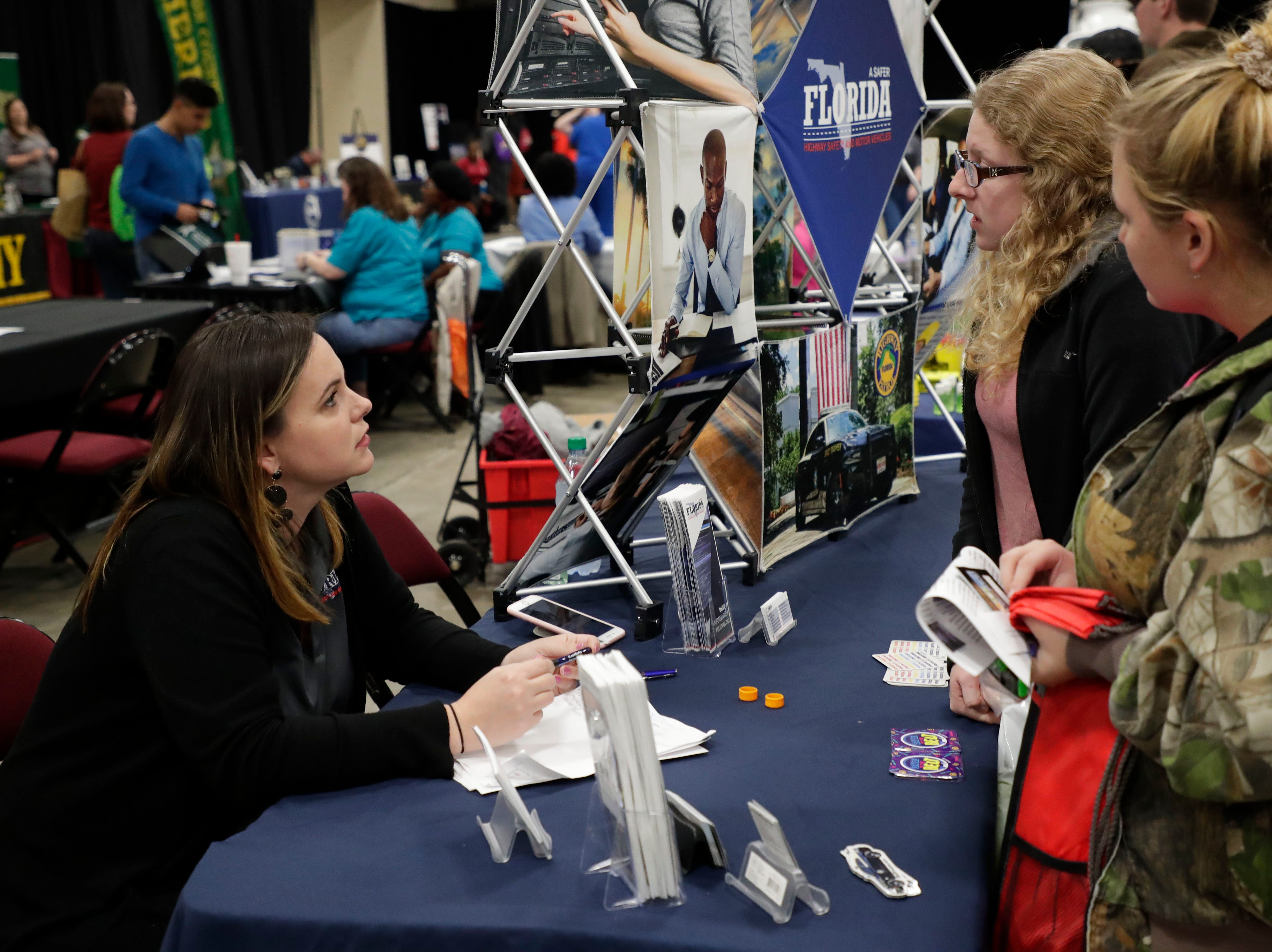 Desiree Aller, lead recruiter for Florida Highway and Patrol, left, talks to Wakulla High School seniors Haley Taylor, center, and Makayla Colvin about a potential career path. High school students throughout Leon County attended the Leon Works Expo at the Tucker Civic Center Friday March 8, 2019.