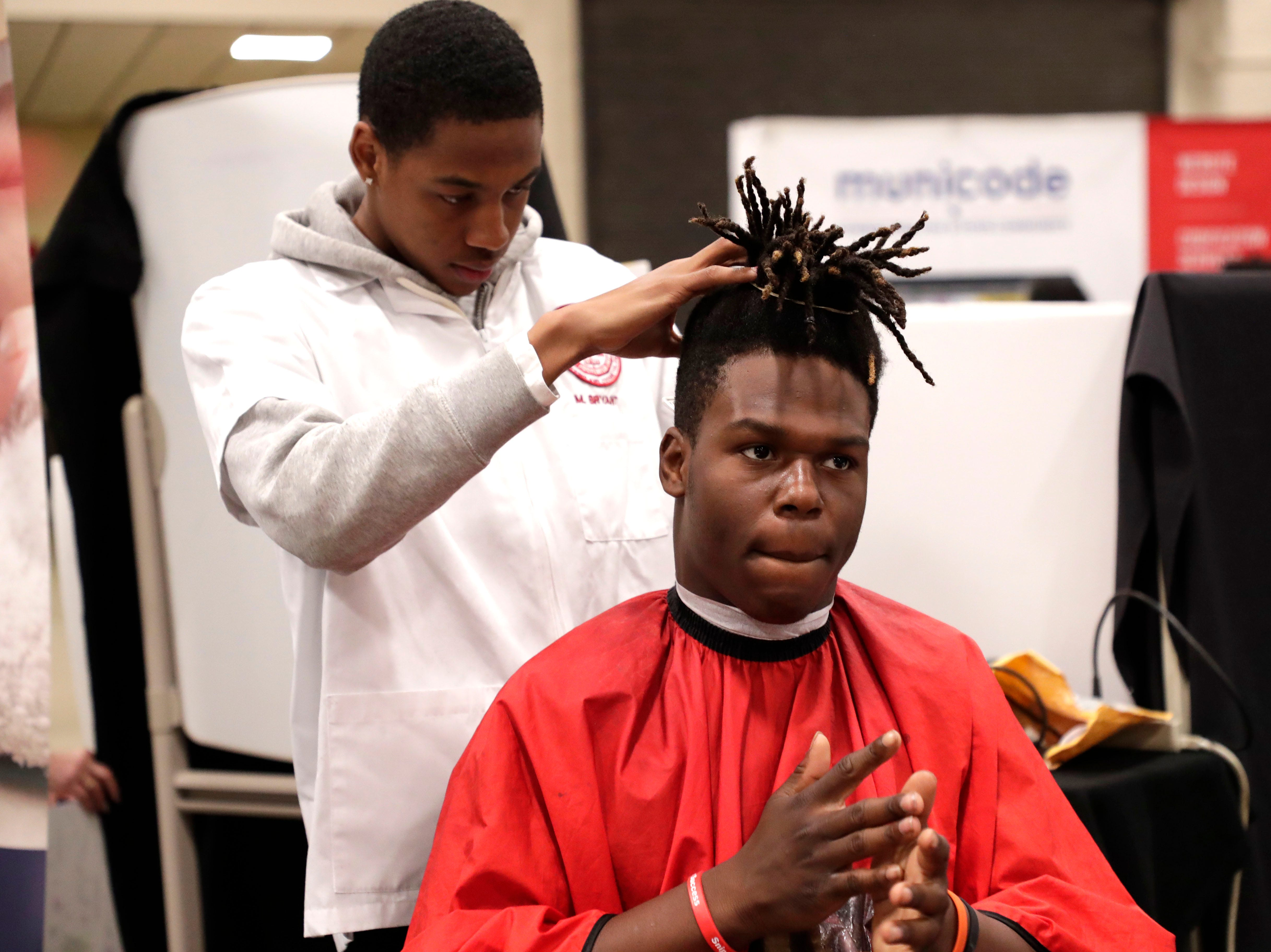 Matthew Bryant, a student in the barber program at the Gadsden Technical Institute, left, trims Amari Alexander's hair. High school students throughout Leon County attended the Leon Works Expo at the Tucker Civic Center Friday March 8, 2019.