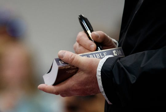 President Donald Trump signs a Bible as he greets people at Providence Baptist Church in Smiths Station, Ala., Friday, March 8, 2019, as they travel to tour areas where tornados killed 23 people in Lee County, Ala.
