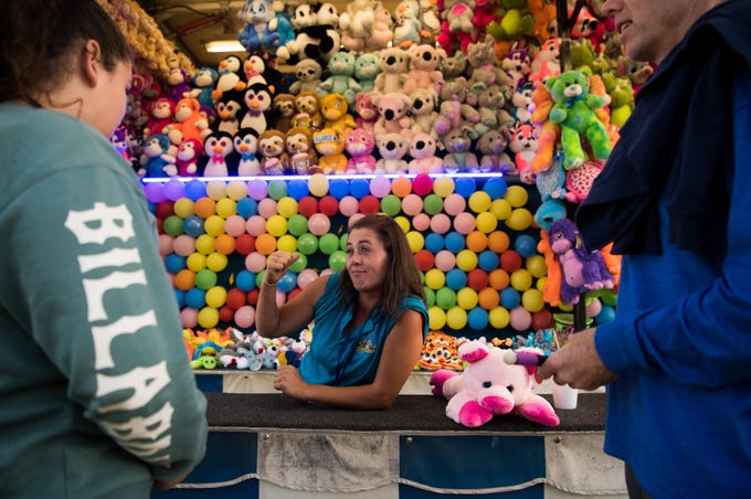 """Josey Gerholt (center), of Cleveland, Ohio, talks about prizes from her game with Sophia Gomez, 13, of Vero Beach, at the Firefighters' Indian River County Fair on opening night Friday, March 8, 2019, at the Indian River County Fairgrounds. Gerholt, who said she is an employee with Cully's Industries, said she has been traveling to work at fairs for four years. """"I like interacting with people and I love my bosses, my bosses are amazing,"""" she said, adding, """"we treat each other like family."""" Gomez was attending the fair with her friend, Bailley McCollom, 12, and father Brad McCollom (right). For more information on the annual event, which runs through March 17, go to www.firefightersfair.org."""