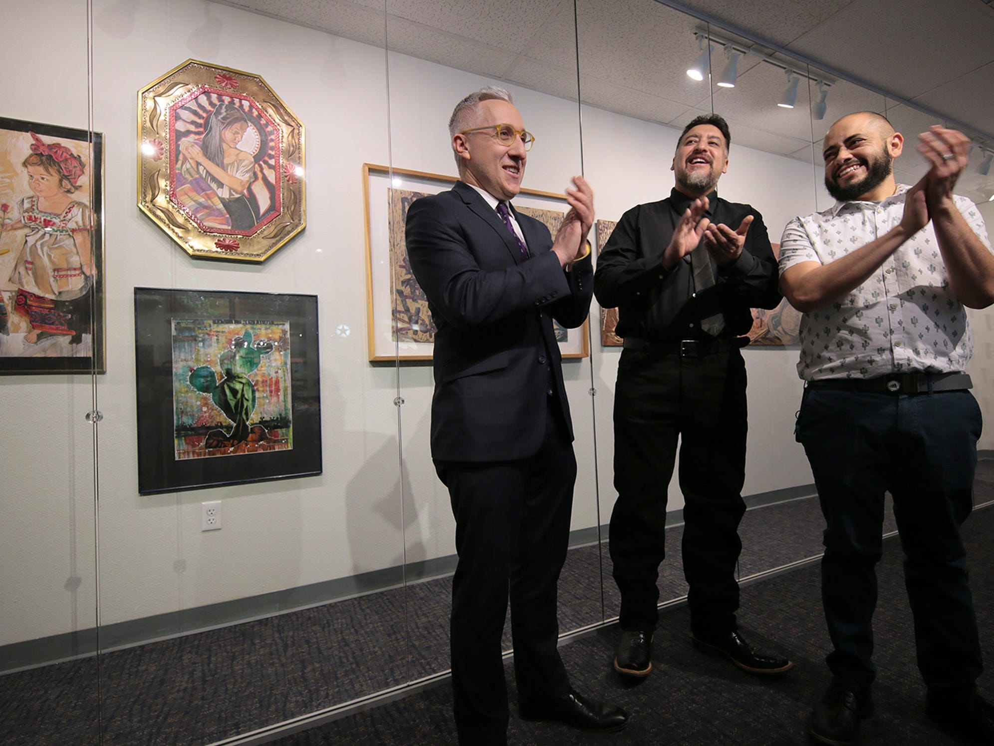 Ben Fyffe, assistant director of the El Paso Museums and Cultural Affairs Department introduces artists Adrian Lopez, right, and Ramiro Ordonez, center, Friday at the Art Windows of El Paso at the El Paso International Airport.
