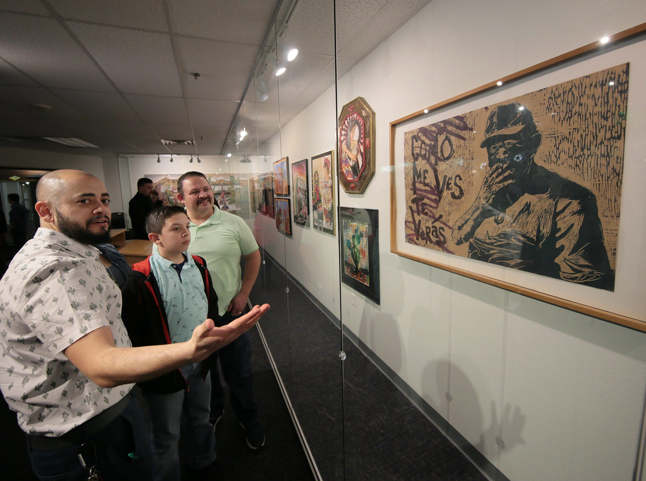 Adrian Lopez shows his print work to his student, Daniel Gomez Jr., 11, and his father at the ribbon cutting for an exhibit of his and Ramiro Ordoñez's artwork Friday, March 8, 2019, at the Art Windows of El Paso at the El Paso International Airport.
