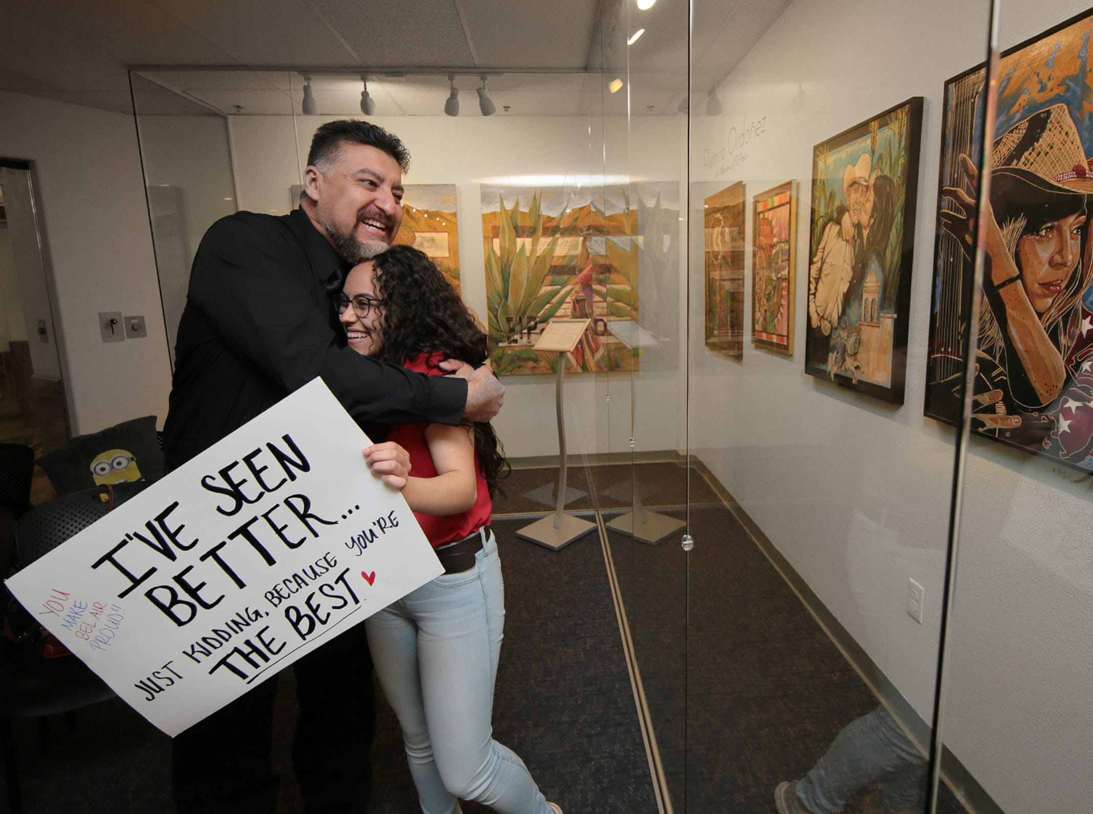 """Artist and art teacher Ramiro Ordoñez hugs his student, Sarah Murillo, who showed up to his gallery opening Friday, March 8, 2019, at the El Paso International Airport with a sign that reads, """"I've seen better."""" The Bel Air High School student said he often jokes that he's seen better when turning in work. Ordoñez and Adrian Lopez opened their exhibit Friday at the Art Windows of El Paso exhibit."""