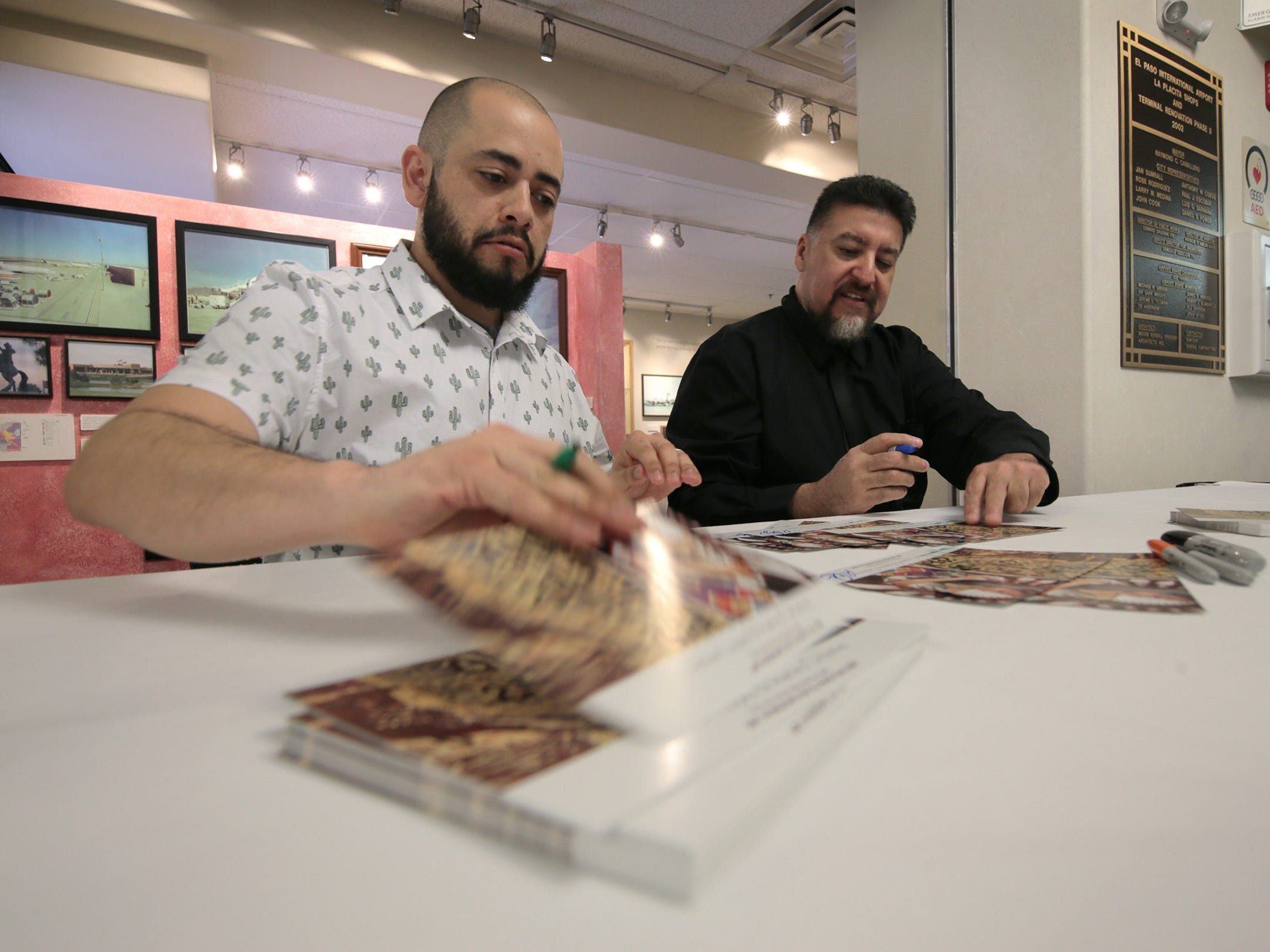 Adrian Lopez, left, and Ramiro Ordonez sign cards after cutting the ribbon on their exhibit at the Art Windows of El Paso Friday.