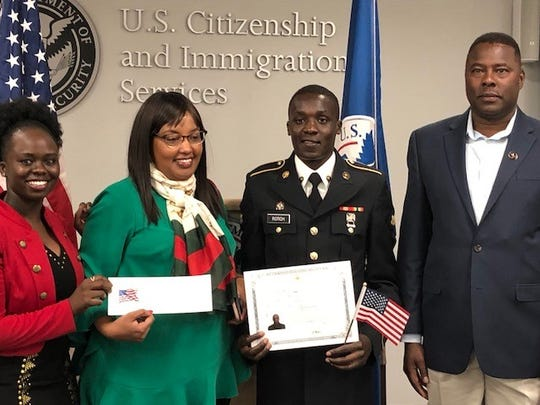 Anthony Rotich shows his certificate of U.S. citizenship after getting sworn in as an American citizen two weeks ago in El Paso. His coach at UTEP, Paul Ereng, is at right.