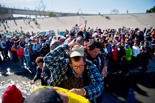 In this Nov. 25 photo, migrants cross the river at the Mexico-U.S. border after pushing past a line of Mexican police at the Chaparral crossing in Tijuana, Mexico, as they try to reach the U.S.