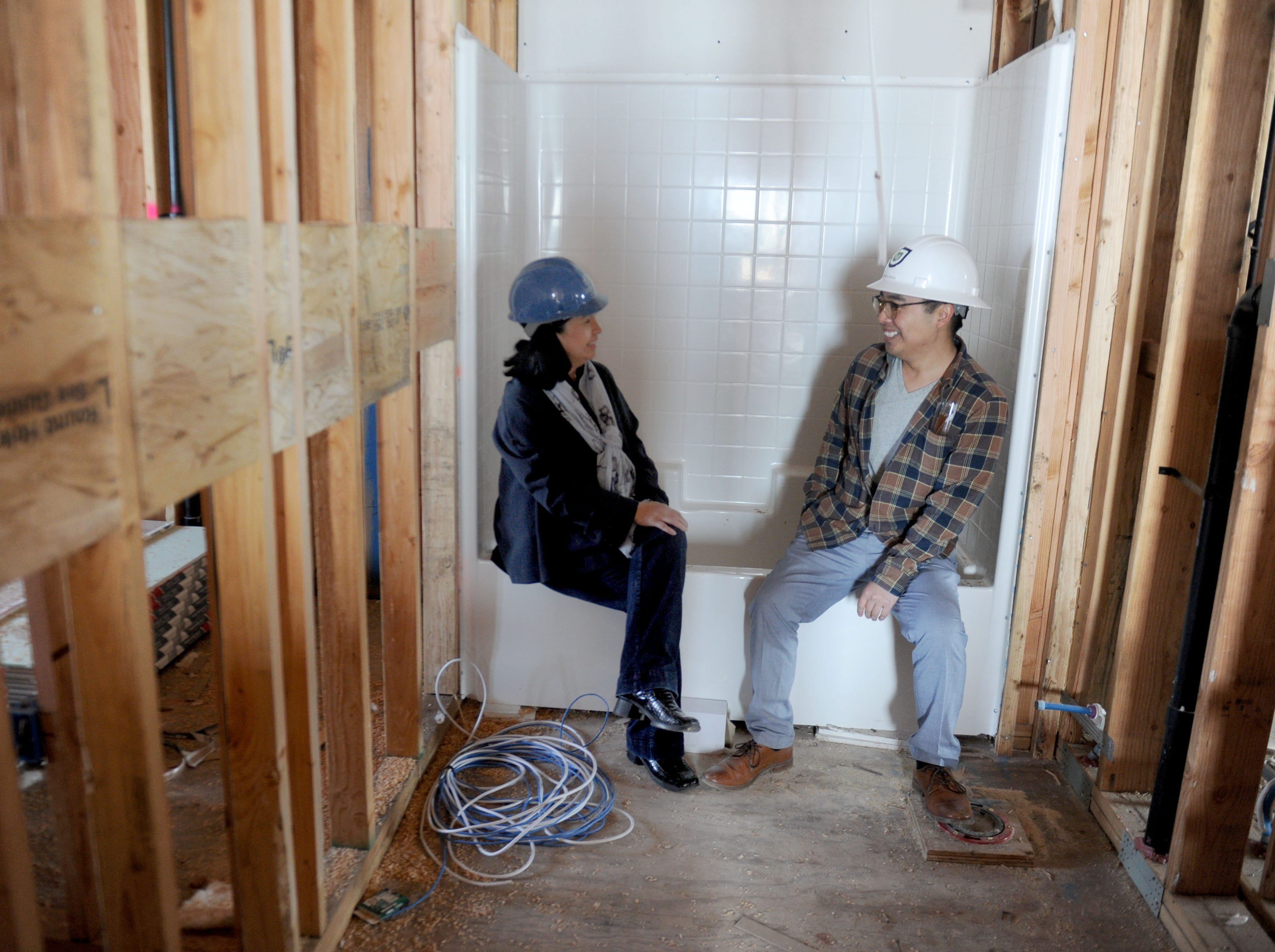 From left, Bambi Hosaka, public relations and marketing manager for Many Mansions, and Derrick Wada, project manager for the Ormond Beach project, talk inside a future bathroom at the veterans housing complex that's under construction in Oxnard. Many Mansions is a local provider of affordable housing.