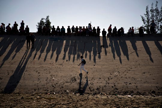 This Nov. 25 photo shows migrants near the Chaparral border crossing watch clashes with U.S. border agents, seen from Tijuana, Mexico. \