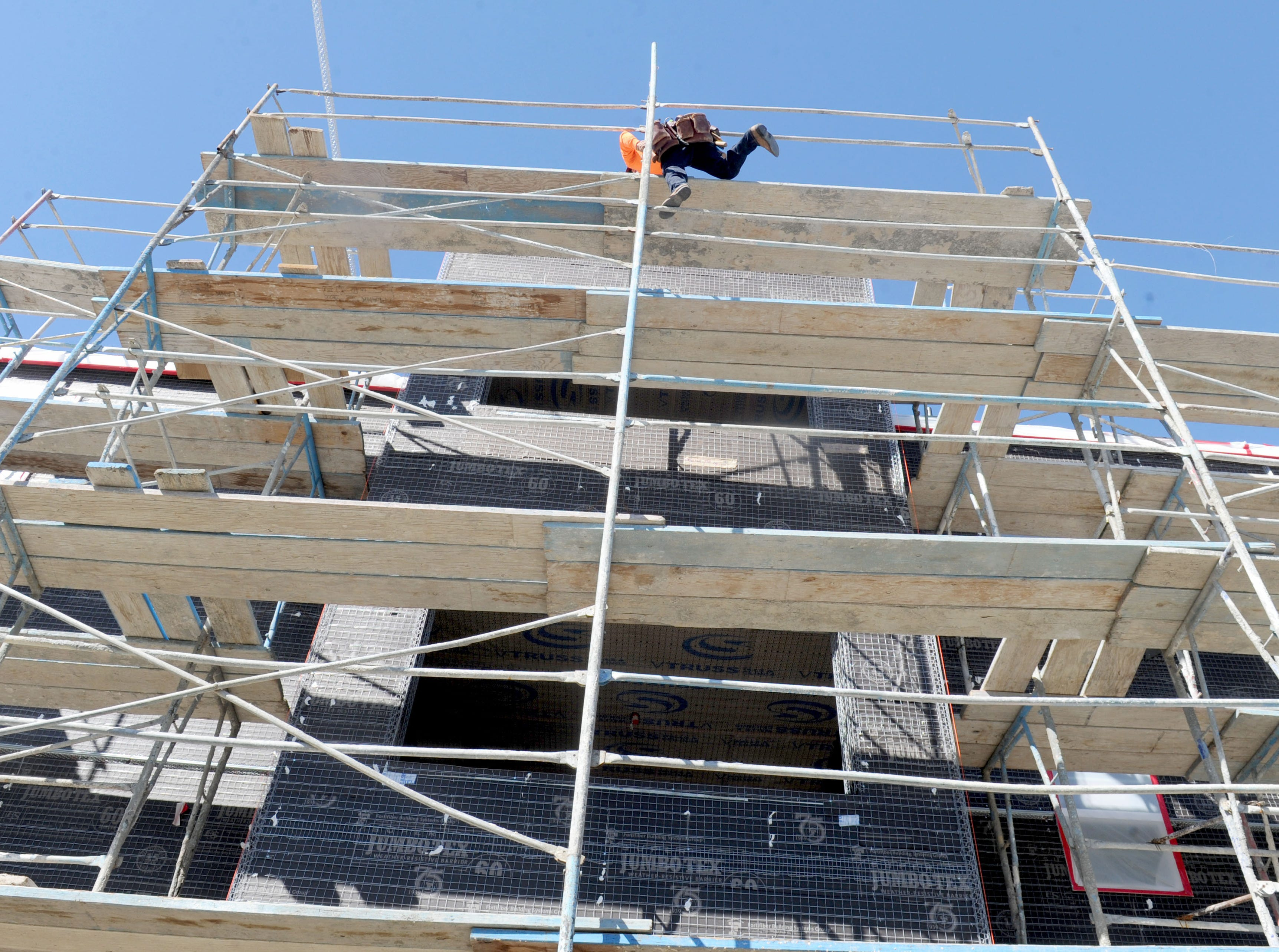 A construction worker climbs to the top of the Ormond Beach veterans housing complex that's under construction in Oxnard for affordable housing provider Many Mansions. The project is scheduled to be completed in August.
