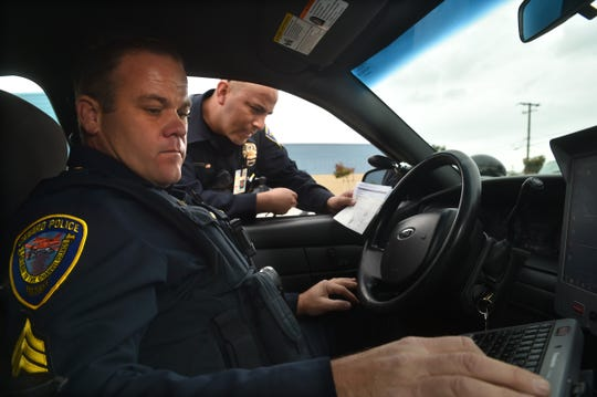 Oxnard police Sgt. Mike Gregson, left, and Officer Fernando Espinoza check the registration of a vehicle that lacked license plates during a recent traffic stop. While Oxnard saw an overall 6 percent decline in crime last year, a 13 percent increase in vehicle thefts was a sour note among the statistics.