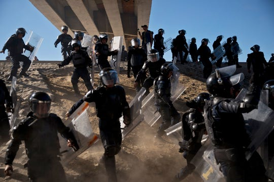 In this Nov. 25 photo, Mexican police run as they try to keep migrants from getting past the Chaparral border crossing in Tijuana, Mexico, near San Ysidro, Calif.