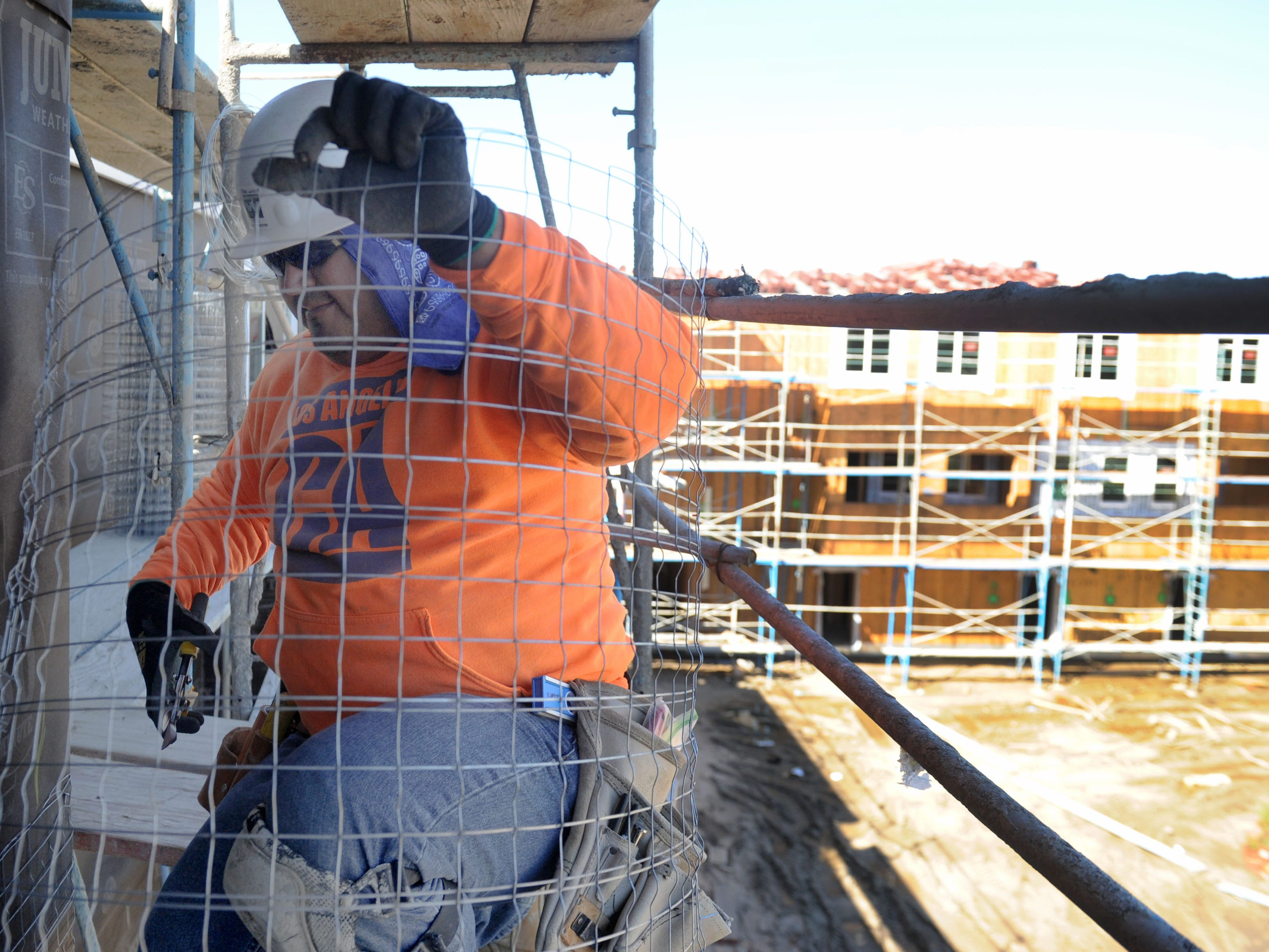 Edwin Ramos cuts stucco support wire at the all-veterans Ormond Beach housing complex being built by Many Mansions in Oxnard. The project is scheduled to be complete in August.