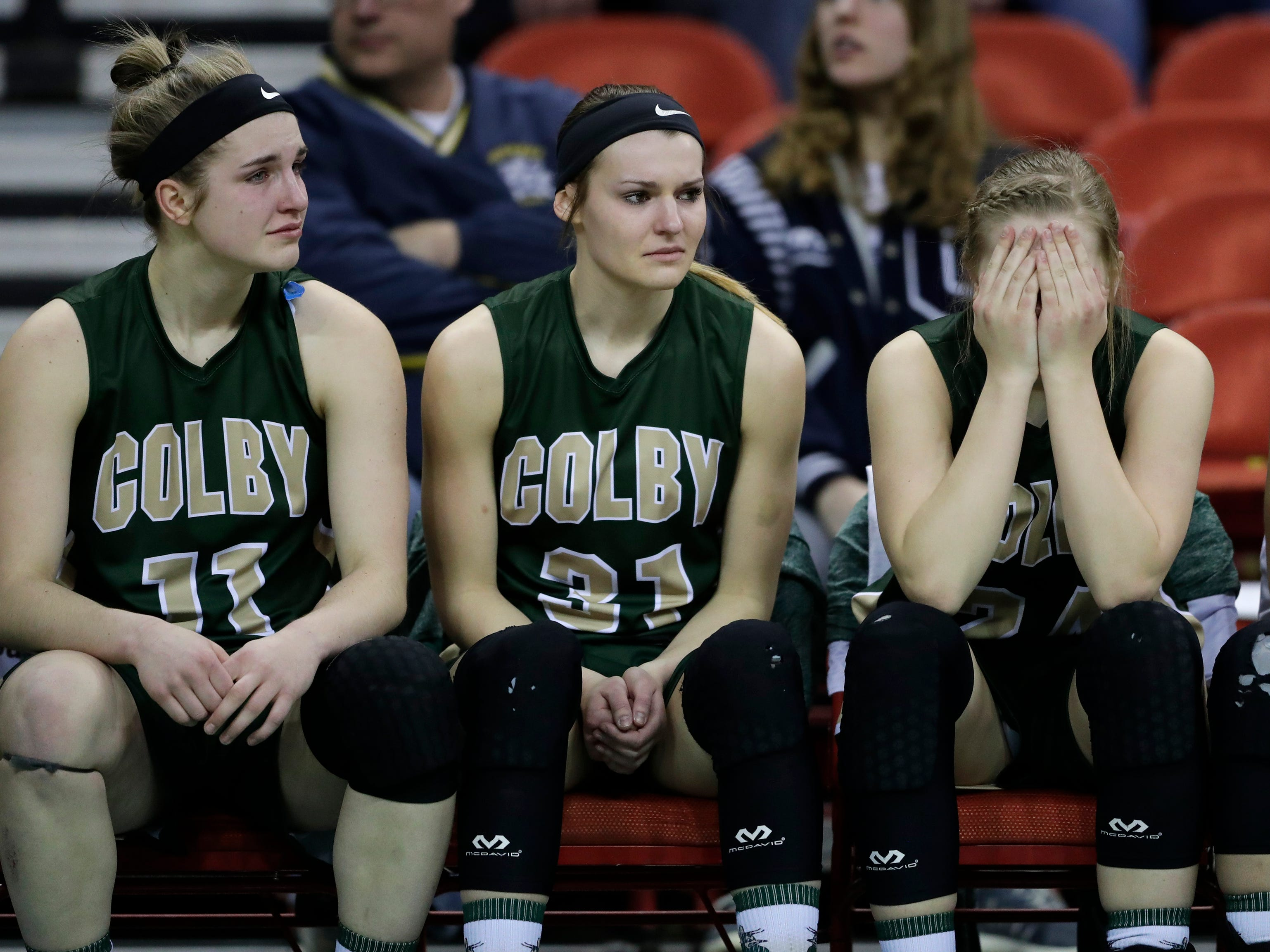 Colby's Hailey Voelker (11),  Alyssa Underwood (31) and Lexi Underwood (24) react in the closing moments against Melrose-Mindoro as during their Division 4 semifinal game at the WIAA girls state basketball tournament Thursday, March 7, 2019, at the Resch Center in Ashwaubenon, Wis.