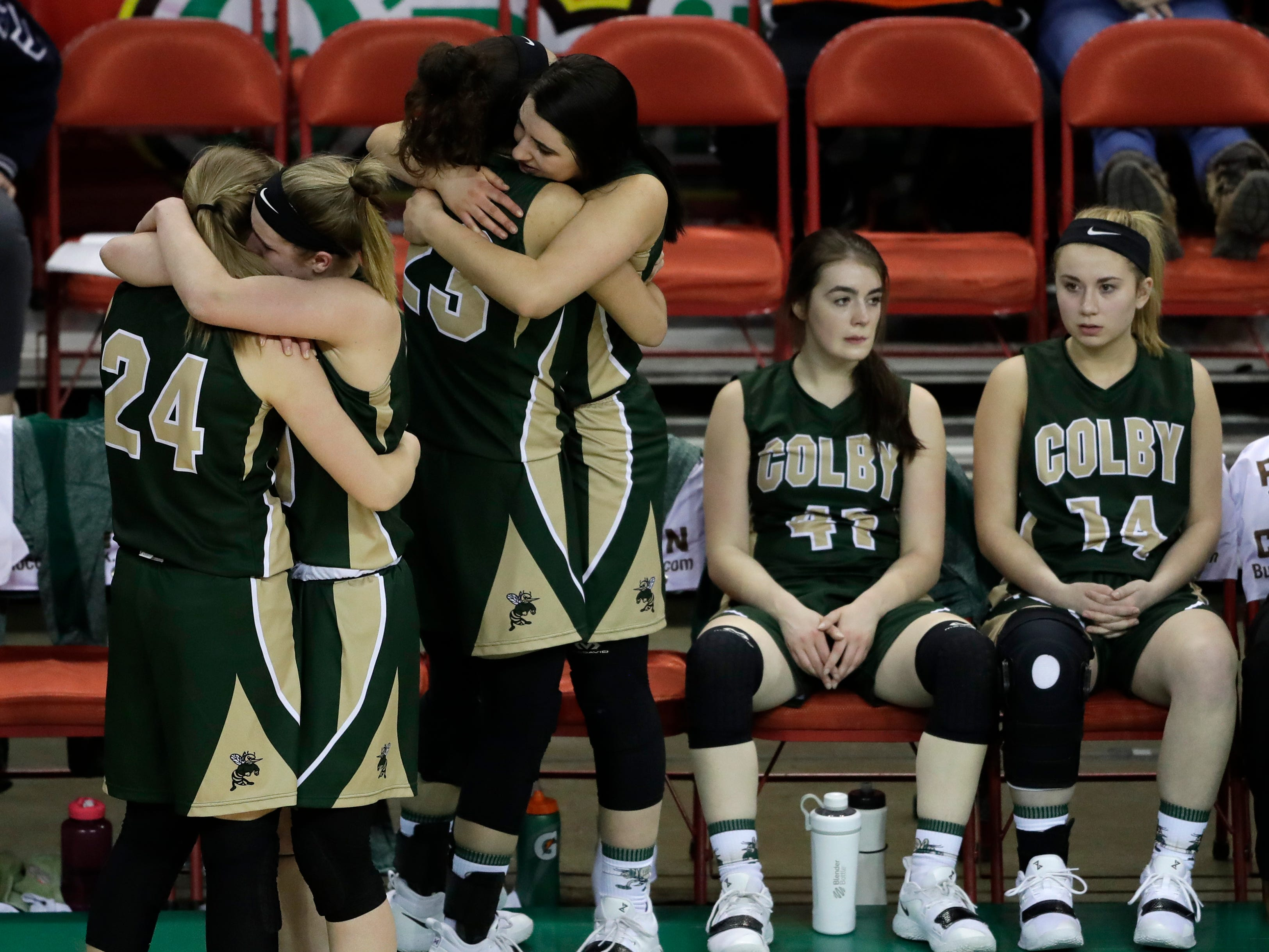 Colby's Lexi Underwood (24) and Hailey Voelker (11) embrace as their teammates Vanessa Lopez (23) and Mackenzie Seemann (21) embrace in the closing minutes against Melrose-Mindoro during their Division 4 semifinal game at the WIAA girls state basketball tournament Thursday, March 7, 2019, at the Resch Center in Ashwaubenon, Wis.
