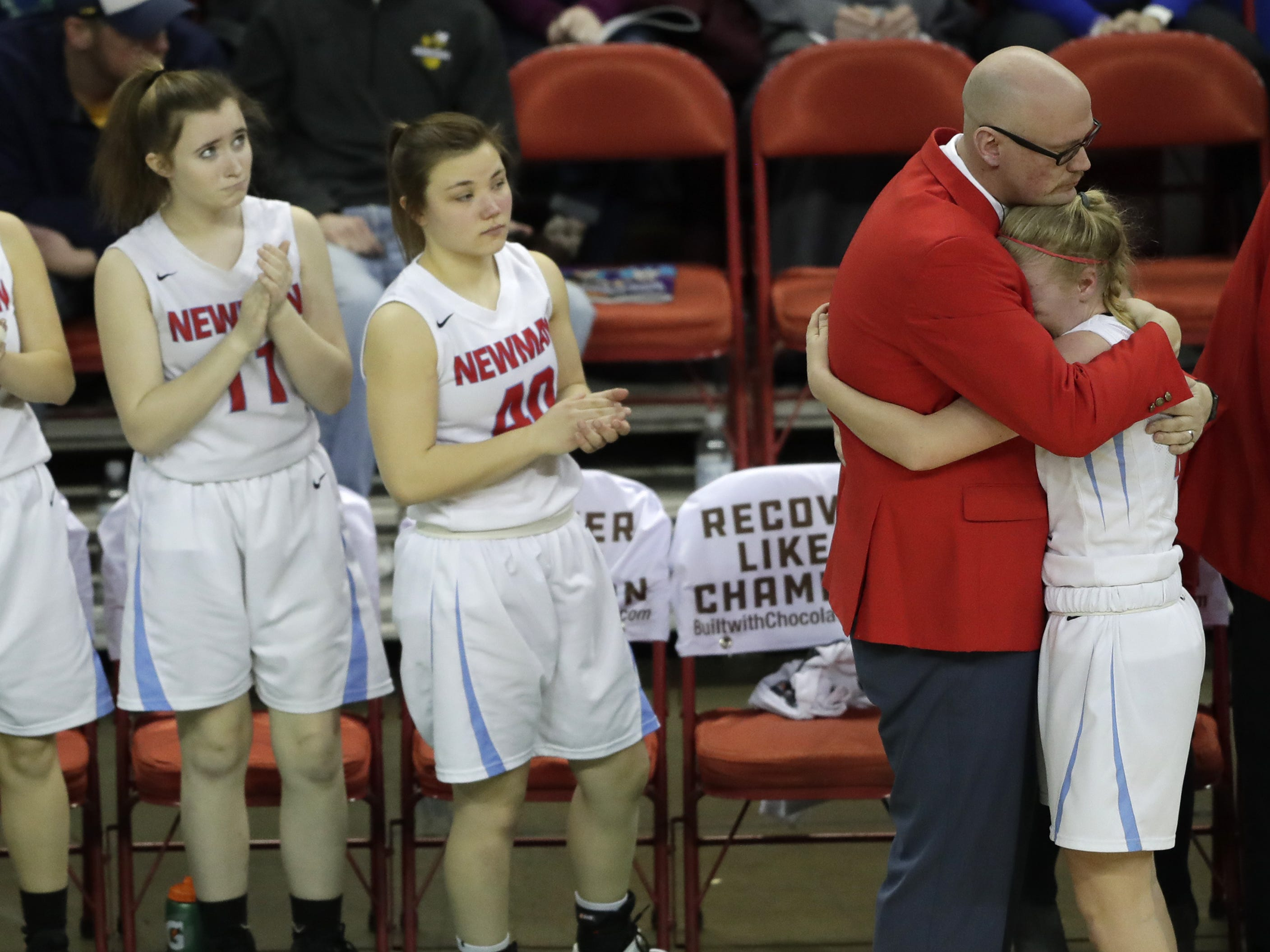 Wausau Newman Catholic's Mackenzie Krach (12) gets a hug from coach Jason Vanden Elzen as she substituted late in the game during their Division 5 semifinal game at the WIAA girls state basketball tournament Friday, March 8, 2019, at the Resch Center in Ashwaubenon, Wis.  Dan Powers/USA TODAY NETWORK-Wisconsin