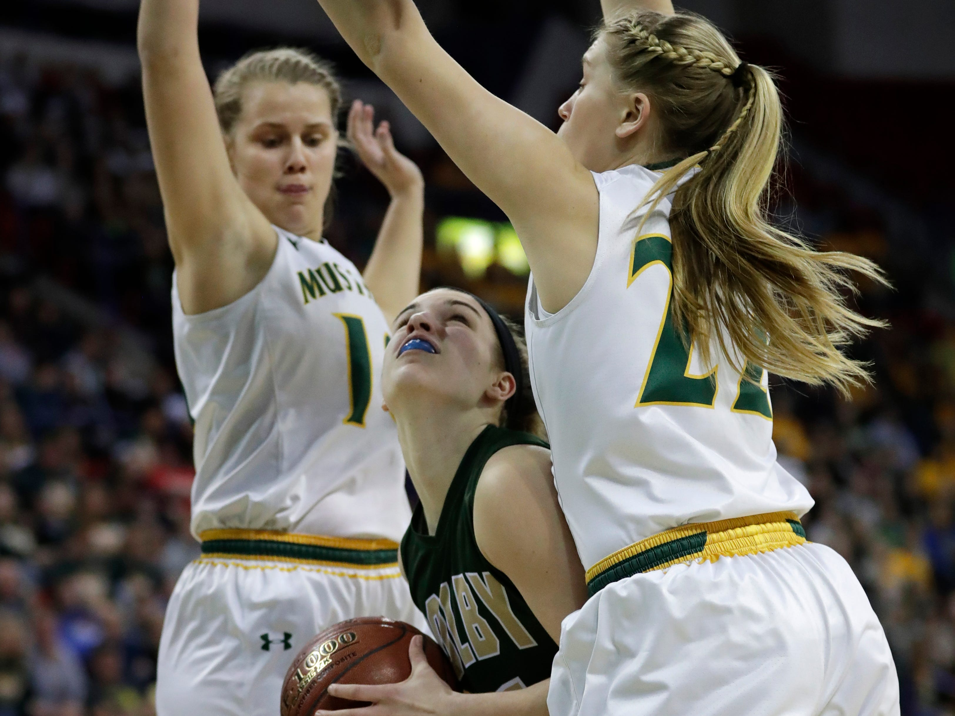 Colby's Hailey Voelker (11) puts up a shot against Melrose-Mindoro's Calette Lockington (10) and Erika Simmons (22) during their Division 4 semifinal game at the WIAA girls state basketball tournament Thursday, March 7, 2019, at the Resch Center in Ashwaubenon, Wis.