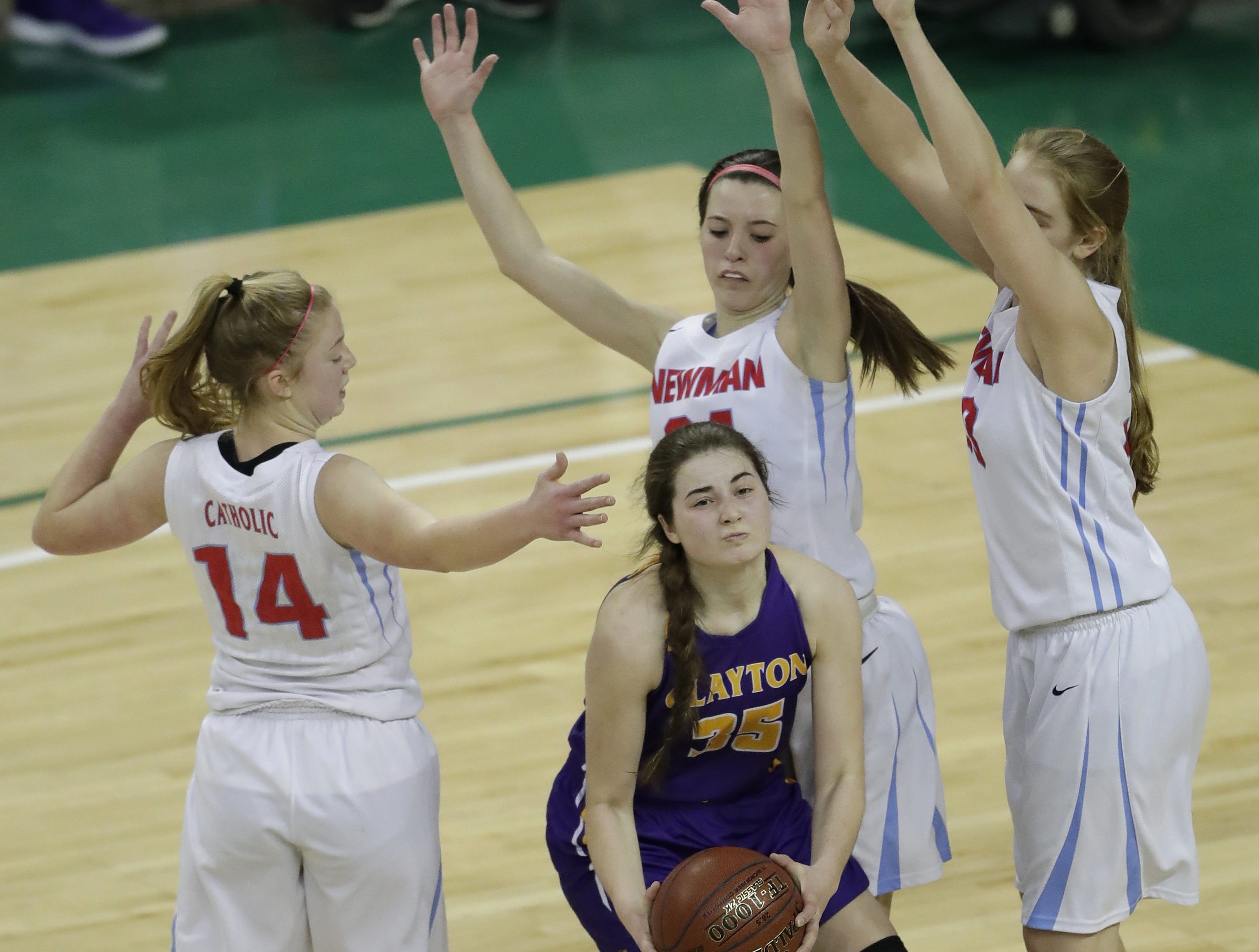 Wausau Newman Catholic's Jaida Heinz (14),  Julia Seidel (34) and Jadelyn Ganski (33) defend against Clayton's Kennedy Patrick (35) during their Division 5 semifinal game at the WIAA girls state basketball tournament Friday, March 8, 2019, at the Resch Center in Ashwaubenon, Wis.  Dan Powers/USA TODAY NETWORK-Wisconsin