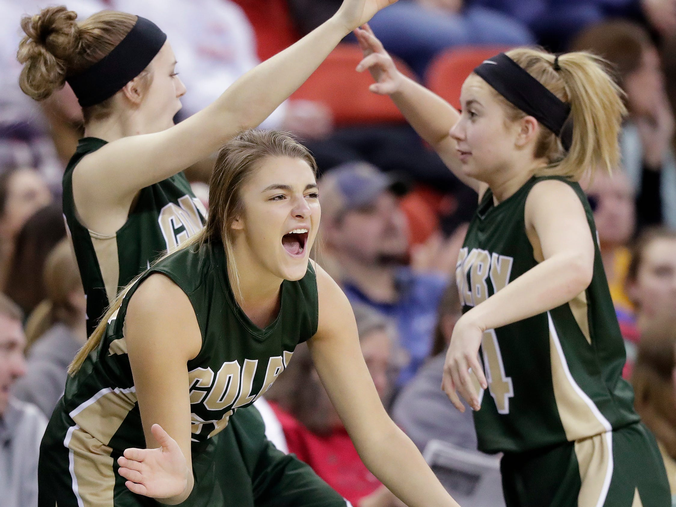 Colby players celebrate a three-point basket against Melrose-Mindoro in a Division 3 semifinal at the WIAA state girls basketball tournament at the Resch Center on Thursday, March 7, 2019, in Ashwaubenon, Wis.