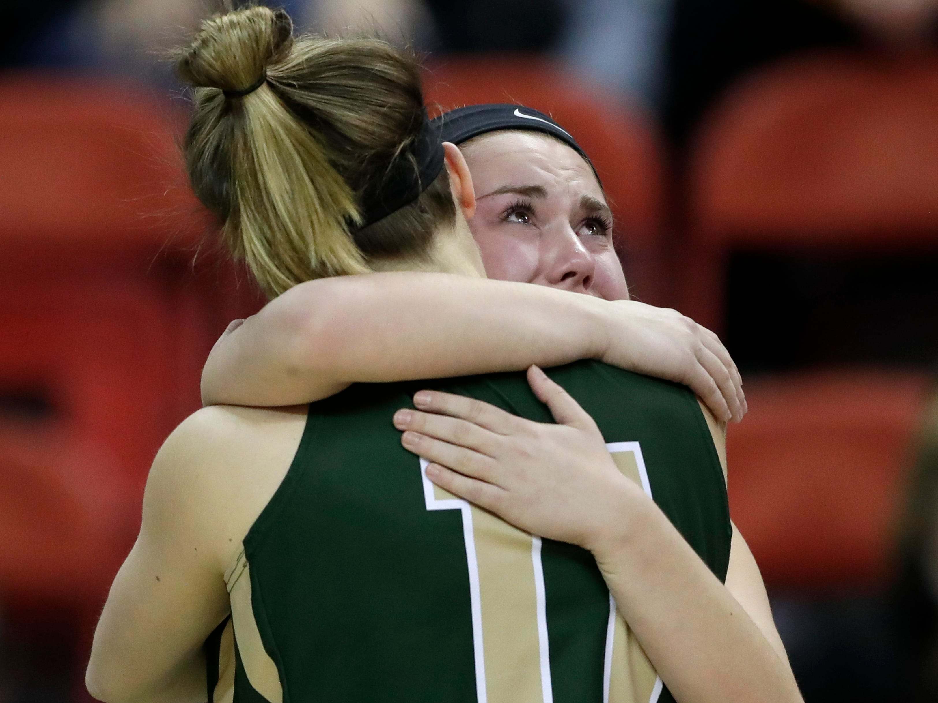 Colby's Hailey Voelker (11) and Kersten Wiese (14) embrace in the closing minutes against Melrose-Mindoro during their Division 4 semifinal game at the WIAA girls state basketball tournament Thursday, March 7, 2019, at the Resch Center in Ashwaubenon, Wis.