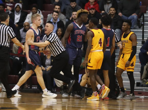 Stepinac's Luke Fizulich is held back after an alteration Joe Toussaint during a CHSAA semifinal basketball game at Fordham University March 7, 2019. Stepinac defeated Cardinal Hayes 77-65.