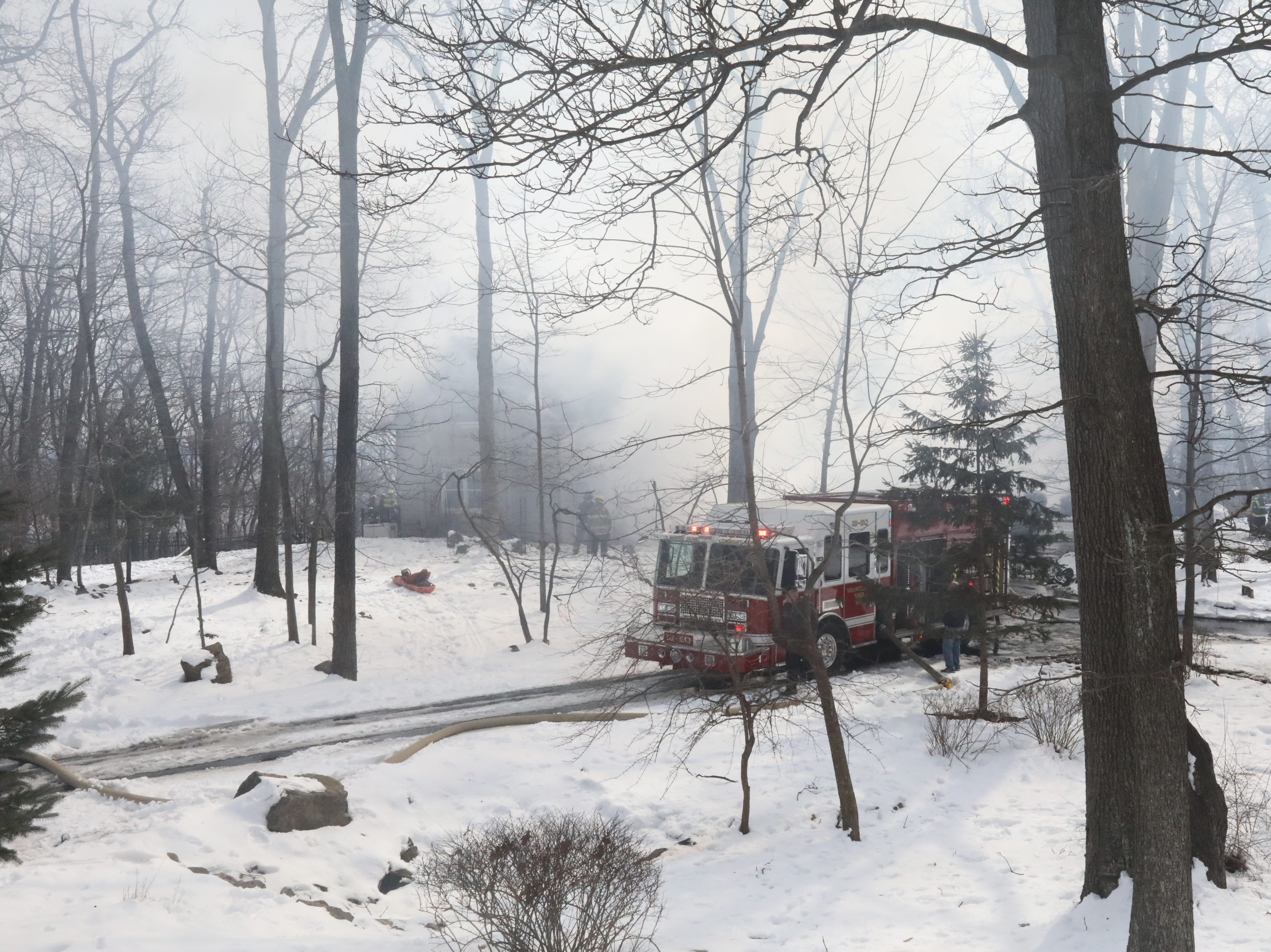 A house is hidden by smoke as firefighters battle the house fire on Soluri Lane in Tomkins Cove on March 8, 2019.