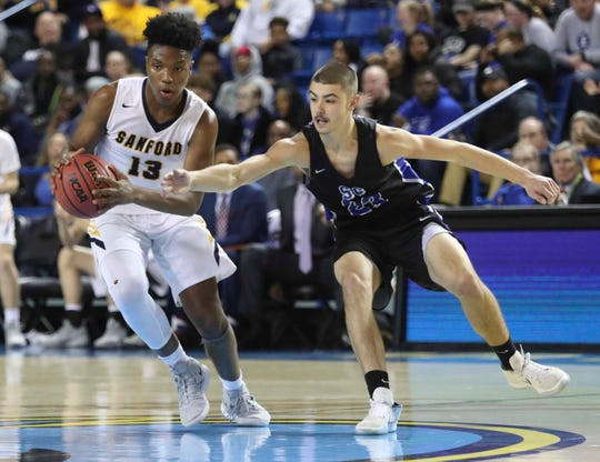 Sanford's Jyare Davis (left) takes the ball across midcourt as St. Georges' Jaymyn Murphy defends in the first half of a DIAA state tournament semifinal at the Bob Carpenter Center Thursday.
