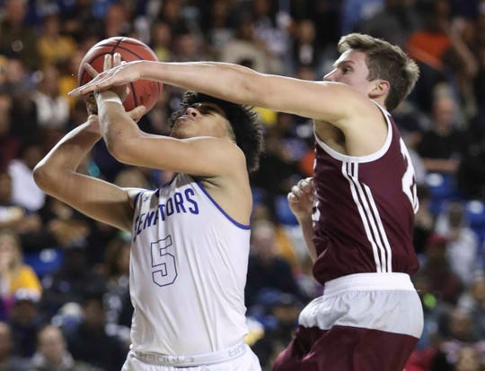 Dover's Elijah Allen (left) scores and is fouled by Caravel's Jeb Williams in the second half of Dover's 68-52 win in a DIAA state tournament semifinal at the Bob Carpenter Center Thursday.