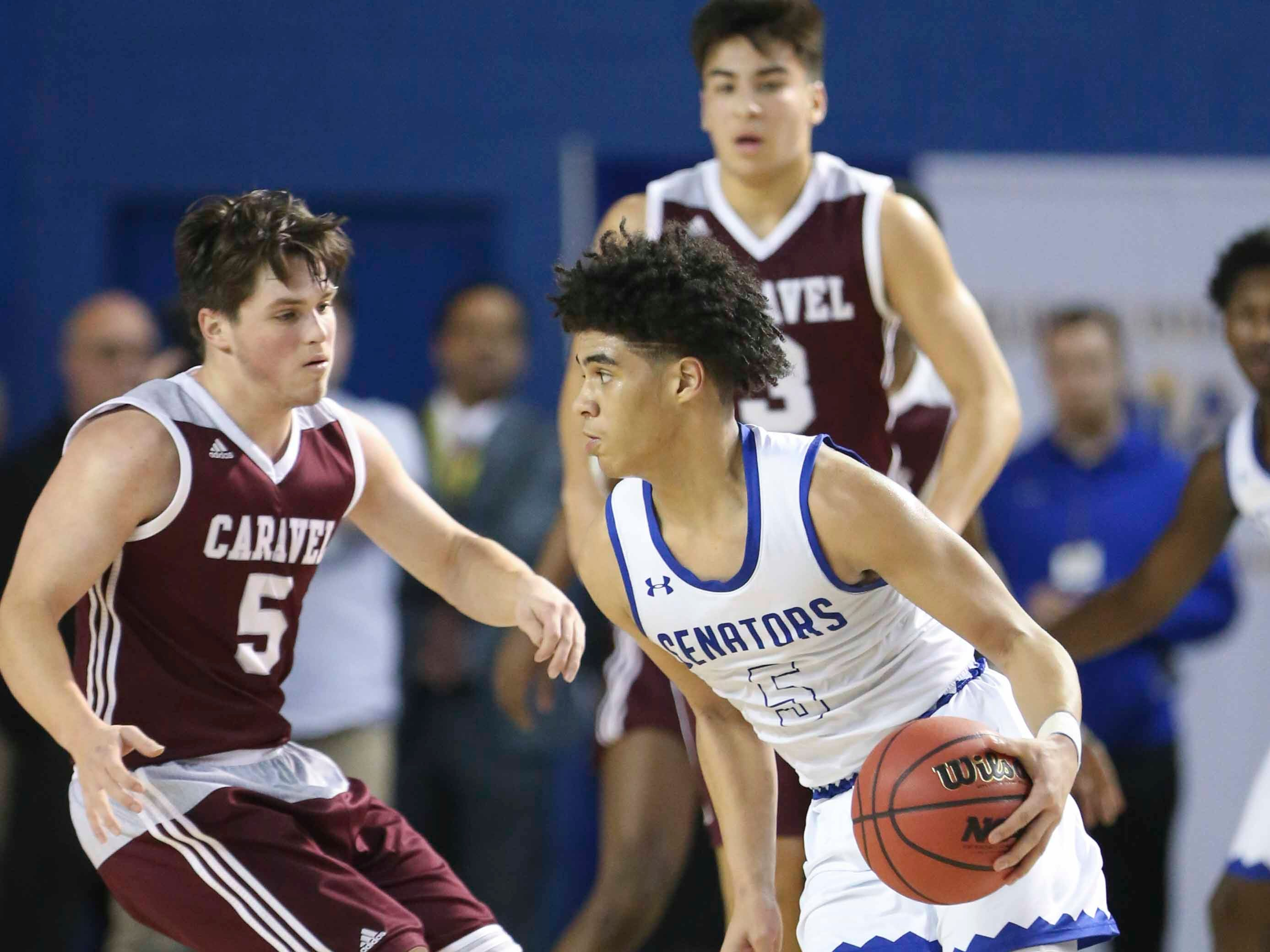 Caravel's Kevin Keister (left) defends against Dover's Elijah Allen in the second half of Dover's 68-52 win in a DIAA state tournament semifinal at the Bob Carpenter Center Thursday.