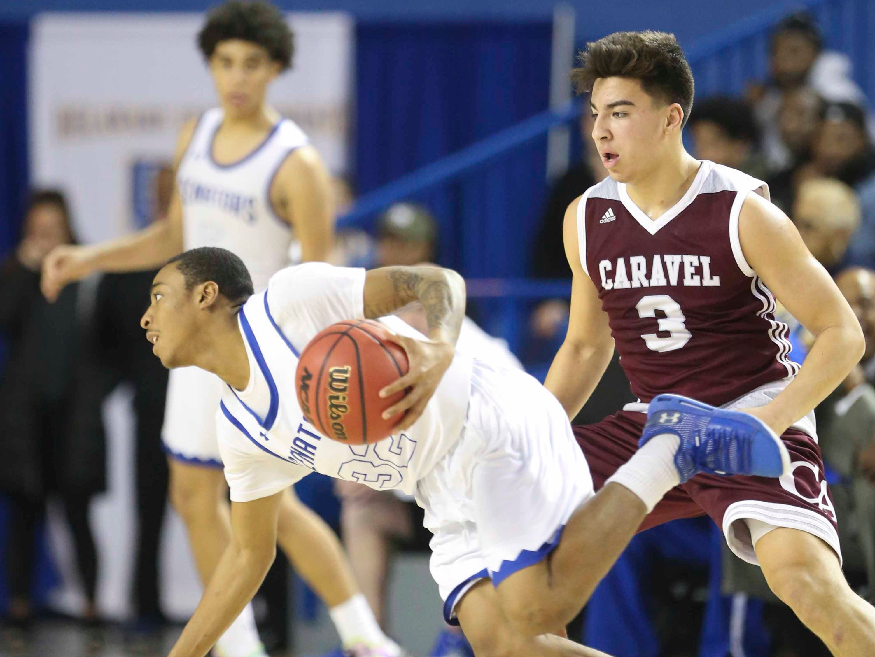 Dover's Wanya Wise (left) dribbles away from Caravel's Brandon Sengphachanh in the second half of Dover's 68-52 win in a DIAA state tournament semifinal at the Bob Carpenter Center Thursday.
