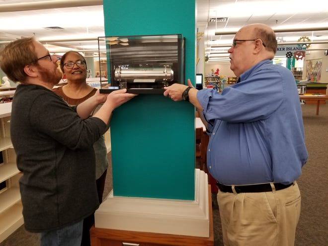 Andrew Jelen, Kim Fawcett, and Jon Walker hang the shadow box containing the time capsule. The box includes instructions directing library staff of the future to open the capsule on June 14, 2118.