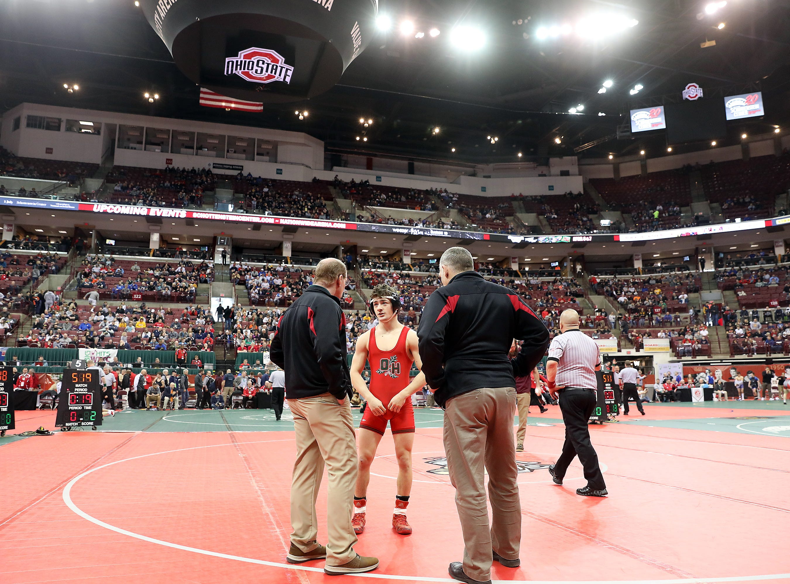 Oak Harbor's Cameron Dickman talks to his coaches during a medical break at the Division III state wrestling tournament on Friday.