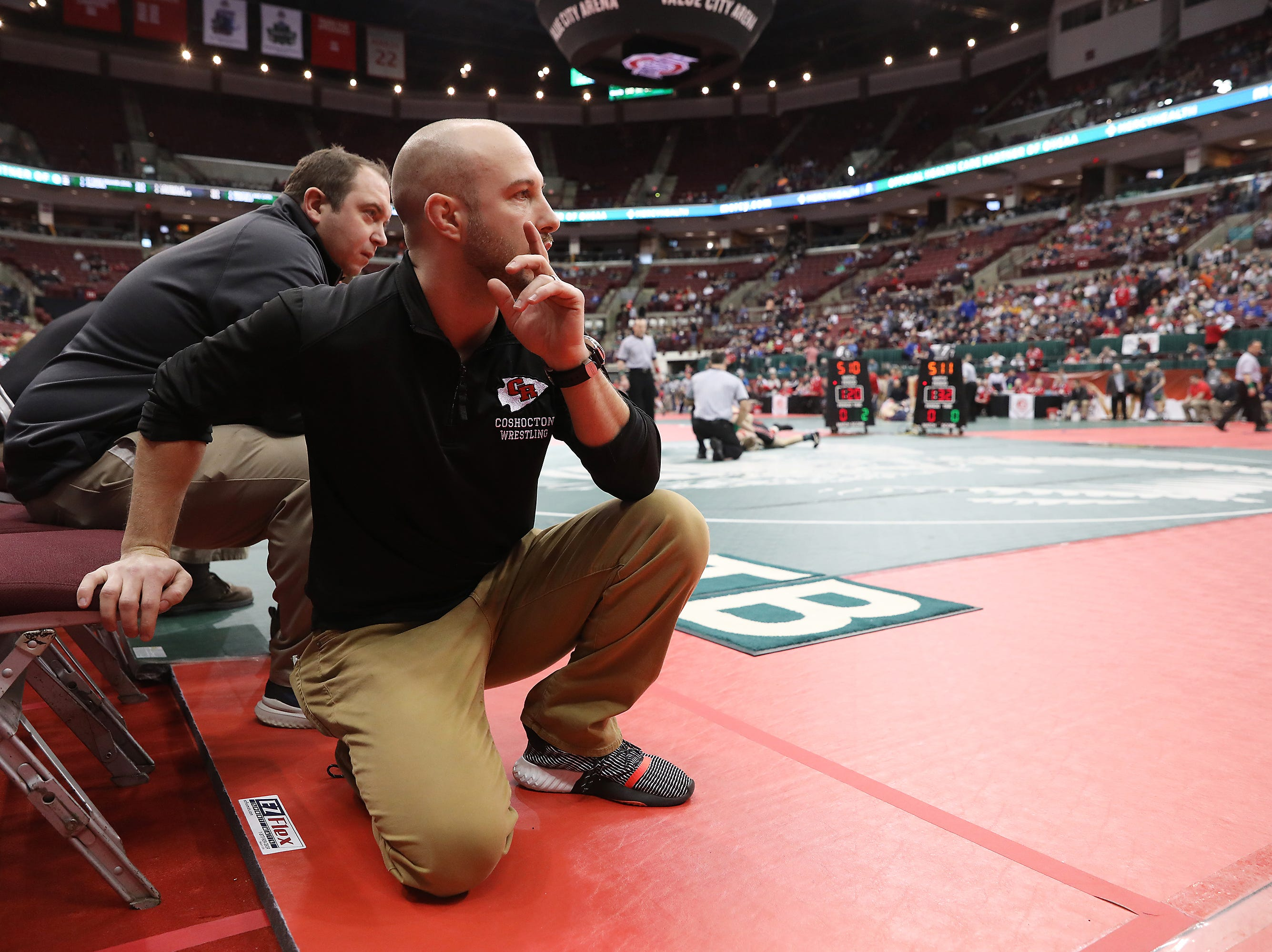 The Coshocton coaching staff encourages Austin Guthrie during his match against Milan Edison's Ray Adams.