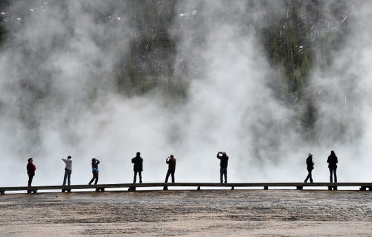 Tourists check out the Grand Prismatic Spring at the Midway Geyser Basin in Yellowstone National Park.