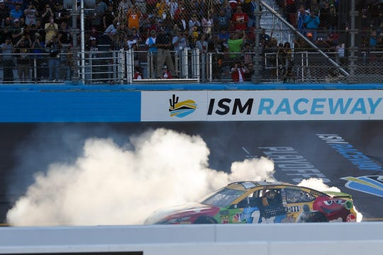 Kyle Busch celebrates after winning the 2018 playoff race at ISM Raceway.