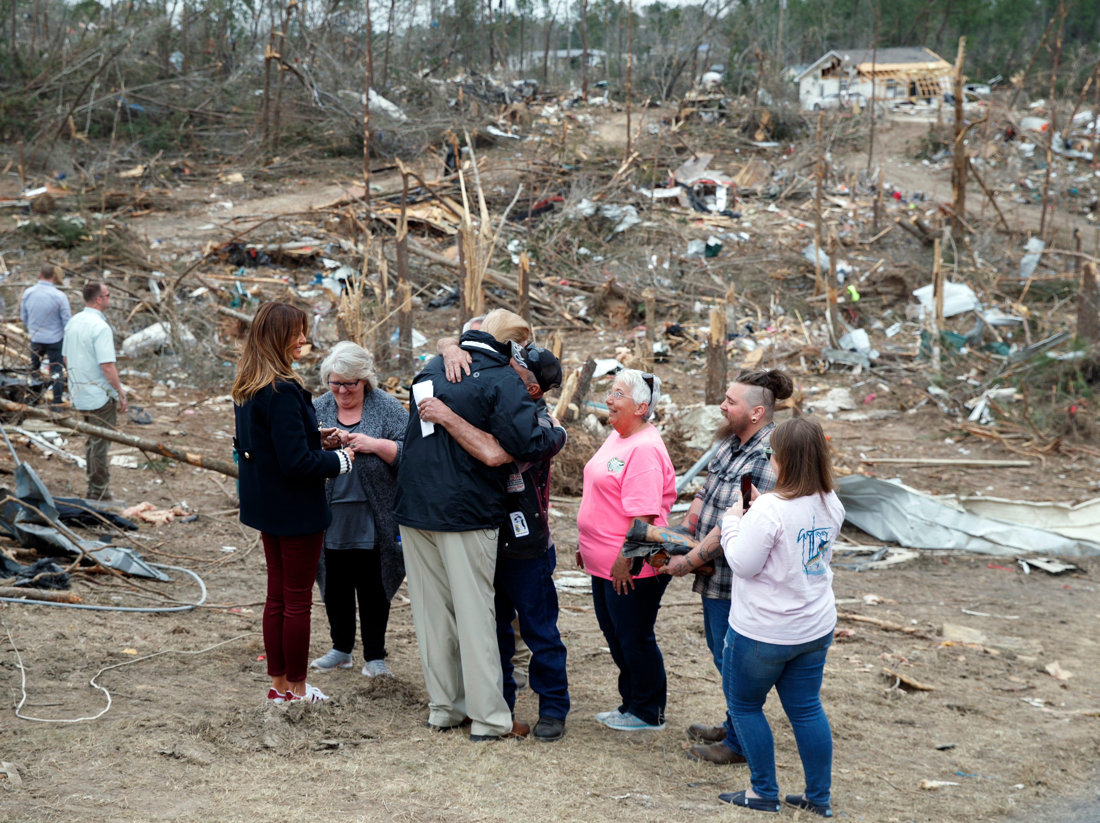 President Donald Trump hugs a resident as he and first lady Melania Trump talk with people Beauregard, Ala., Friday, March 8, 2019, as they travel to tour areas where tornados killed 23 people in Lee County, Ala.